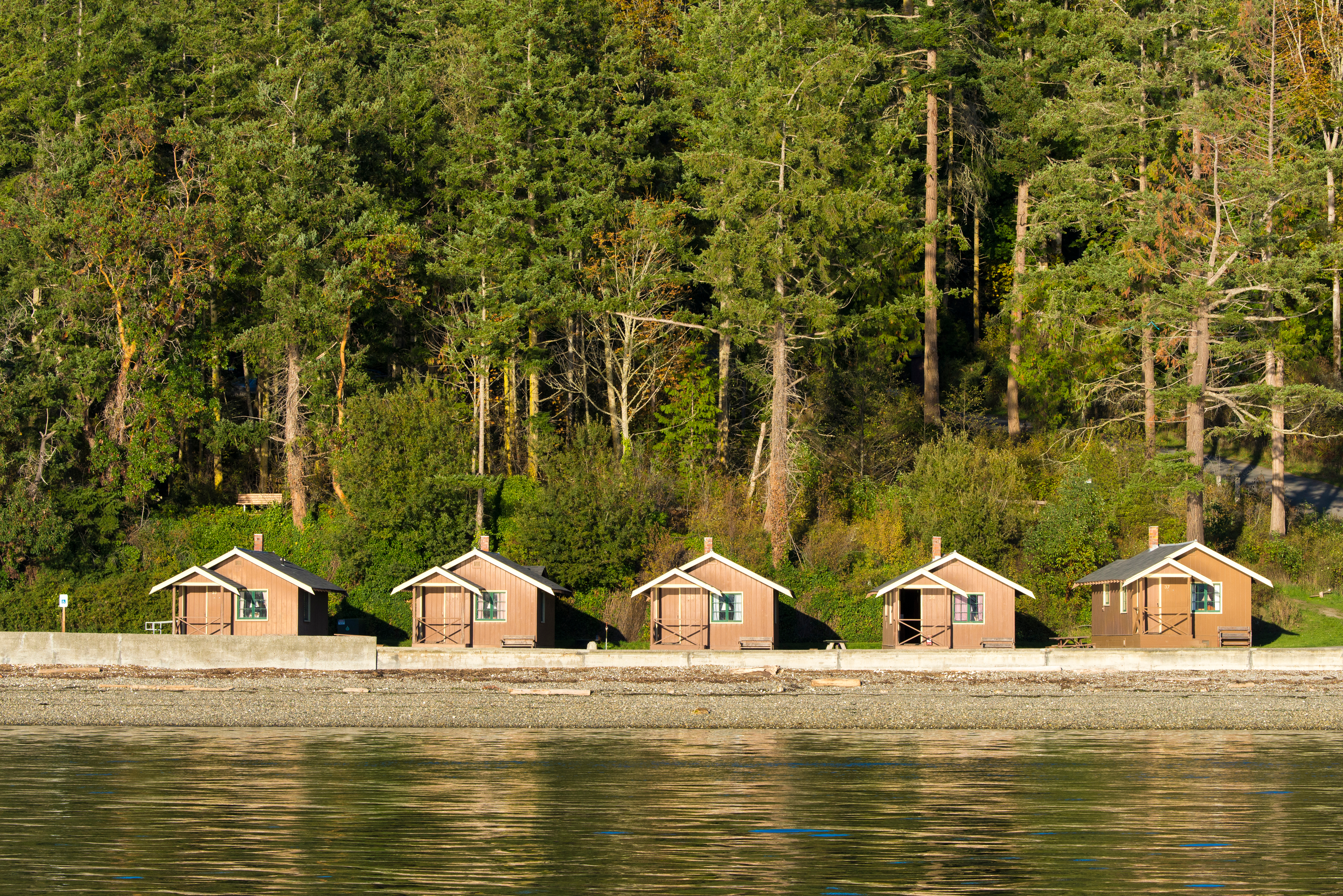 In the foreground is a body of water. In the distance is a row of small wooden cabins. Behind the cabins is a forest with many trees.