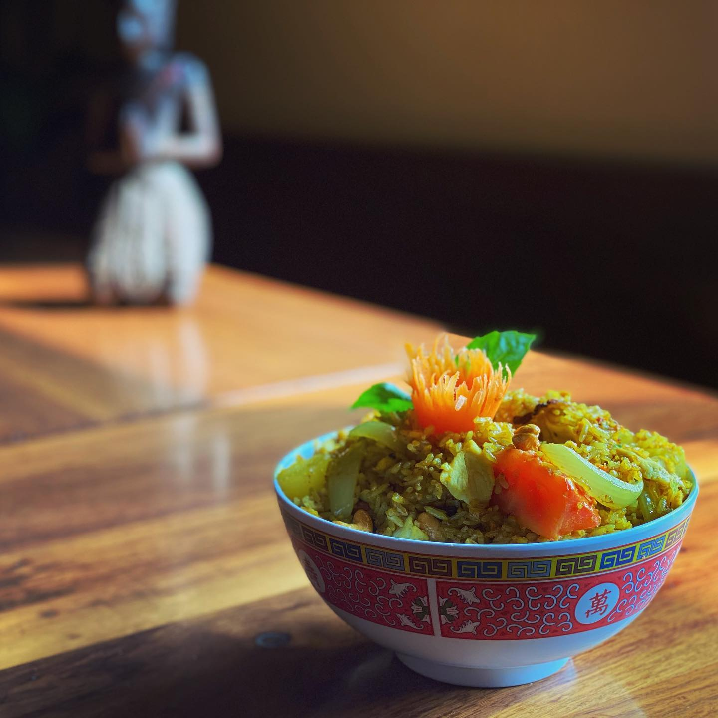 A small bowl is filled with yellow rice studded with tomatoes on a wooden table with a stone buddha in the background