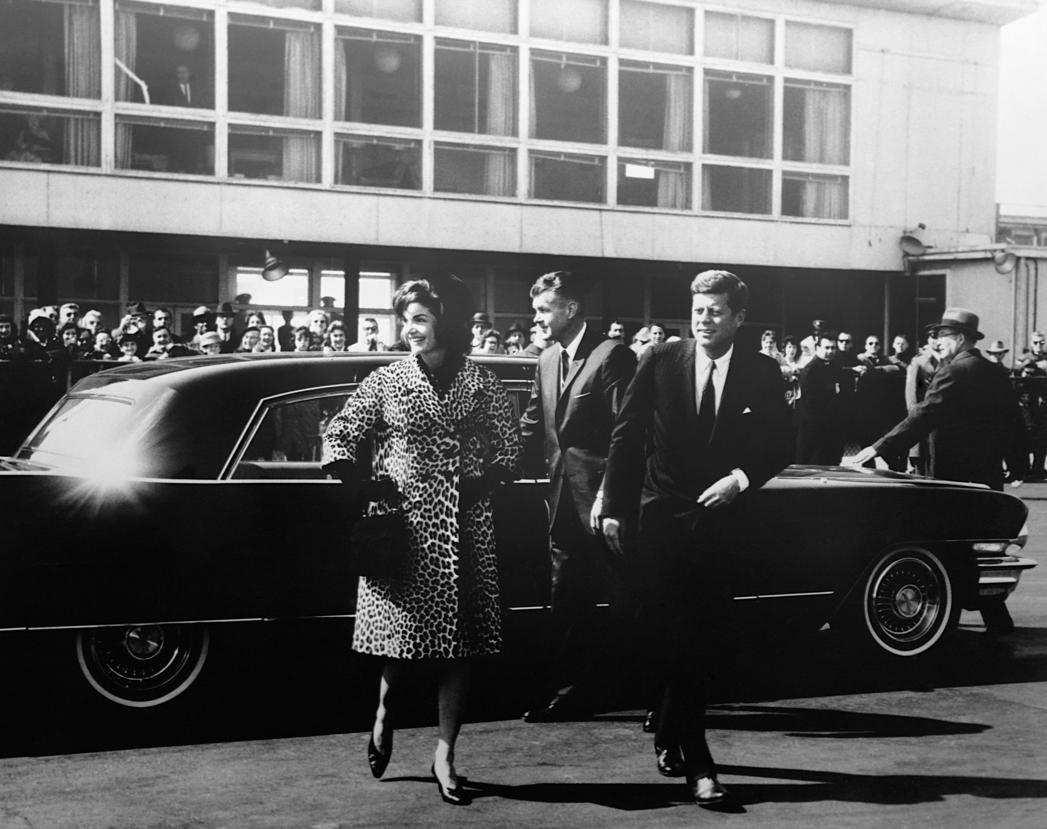 Jackie Kennedy in a leopard print coat standing in front of a car with JFK.
