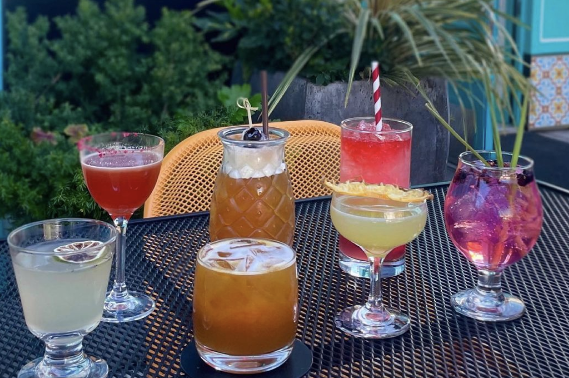A selection of seven colorful cocktails at Ba Bar on a patio table