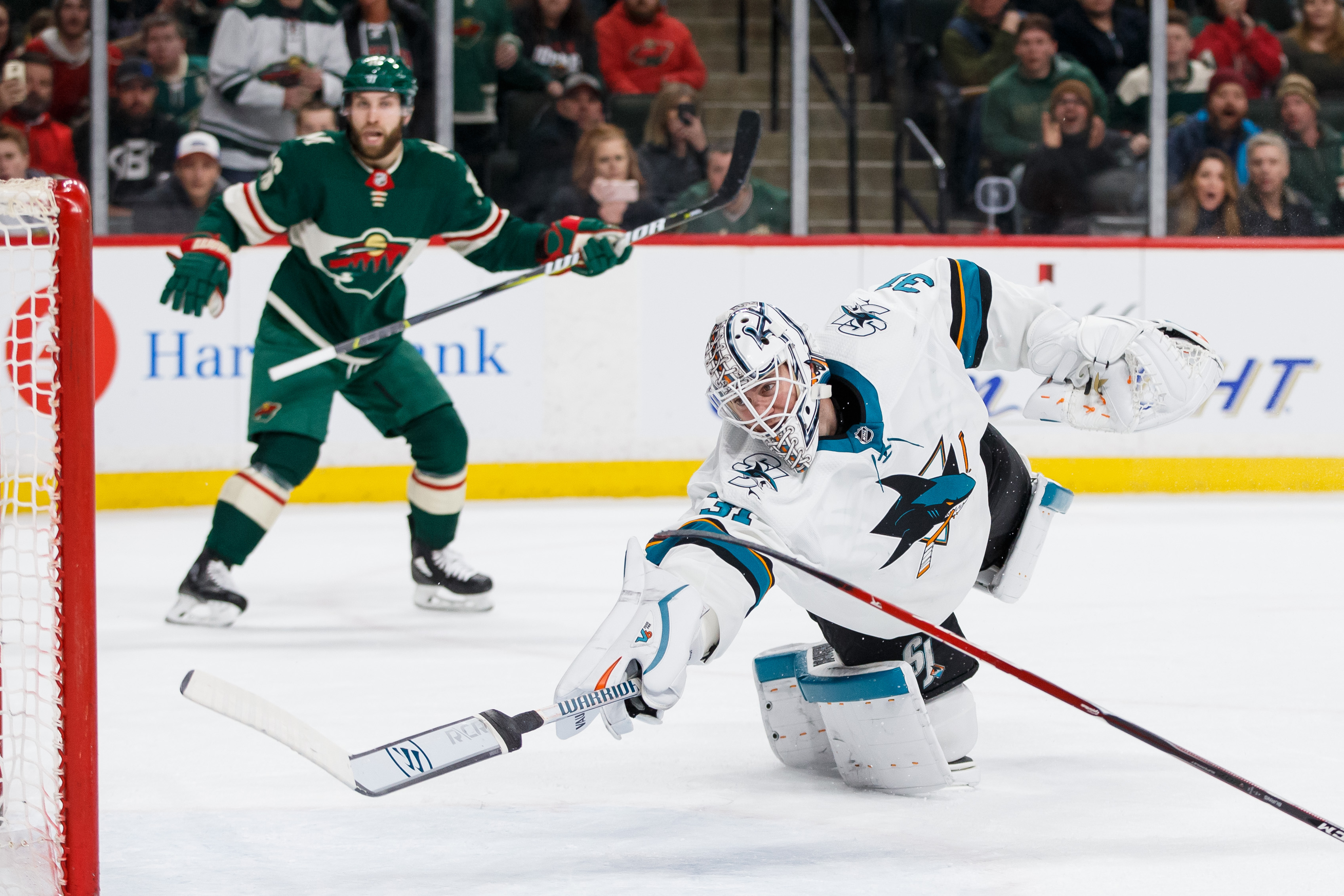 Feb 25, 2018; Saint Paul, MN, USA; San Jose Sharks goalie Martin Jones (31) dives to make a save in overtime against the Minnesota Wild defenseman Jared Spurgeon (46) at Xcel Energy Center.