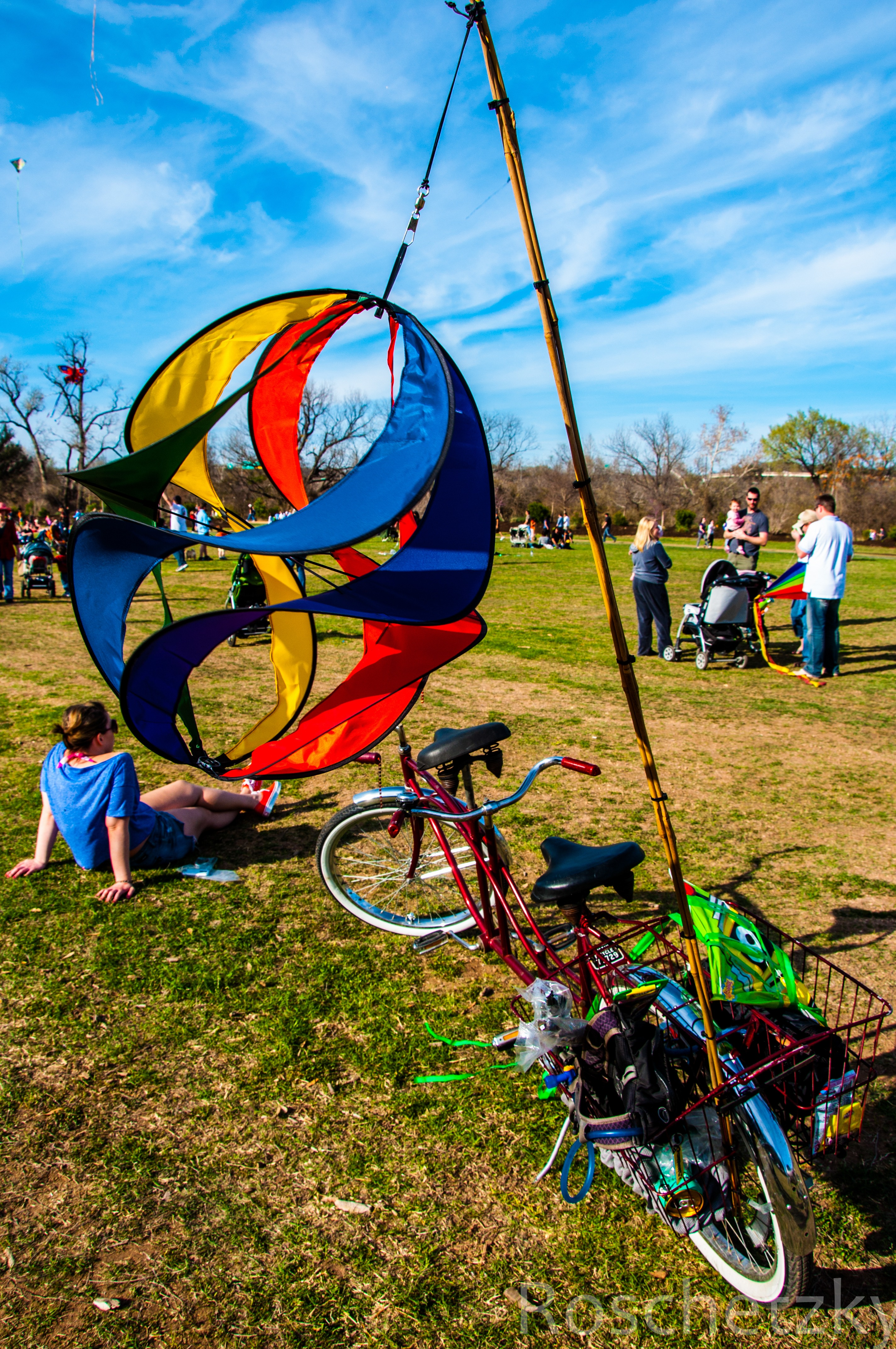 Person sitting on ground with big colorful kite and vintage bikes
