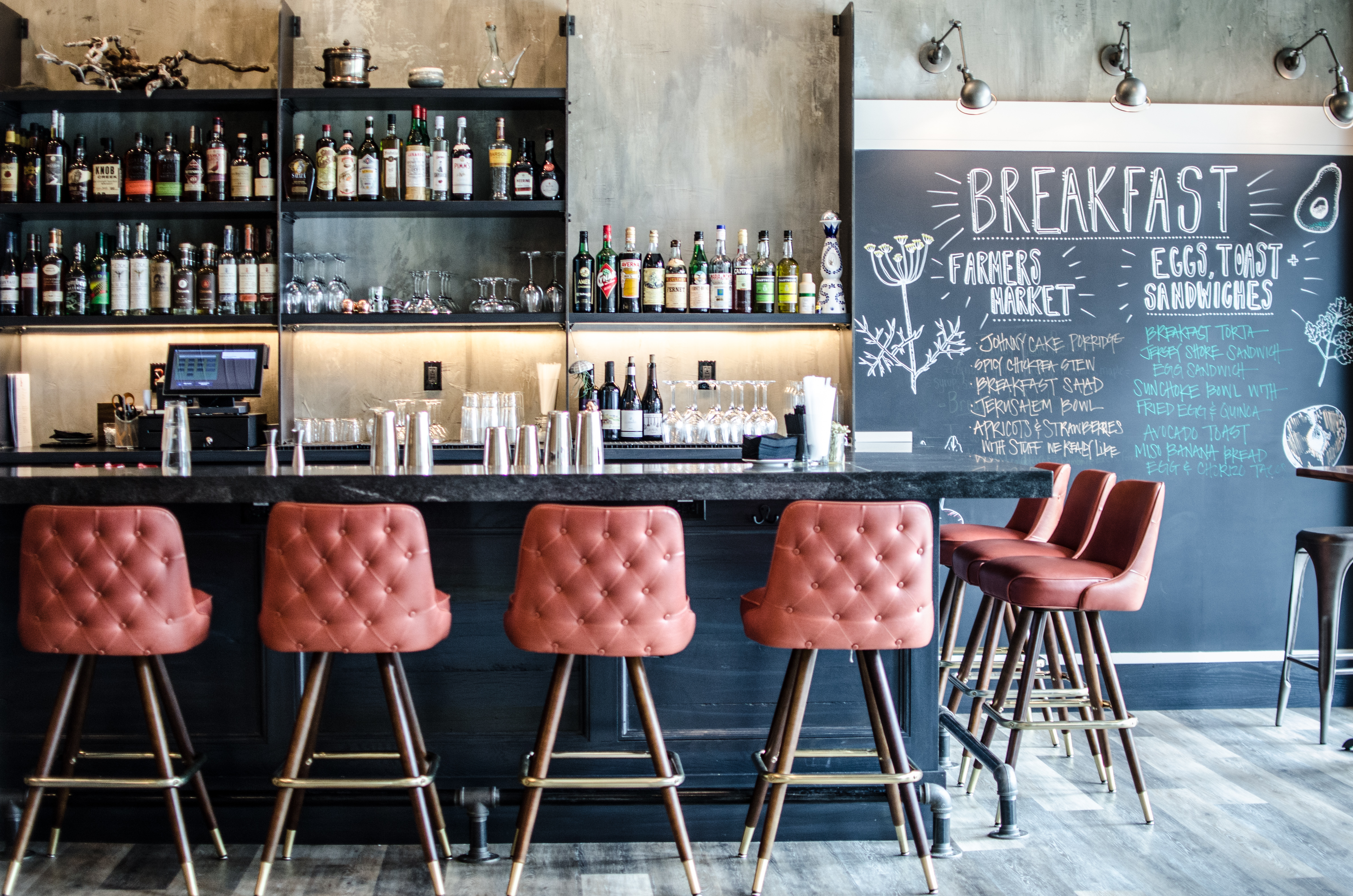 Pale red cushioned barstools line a black bar behind which stands a wall and shelving for liquor bottles
