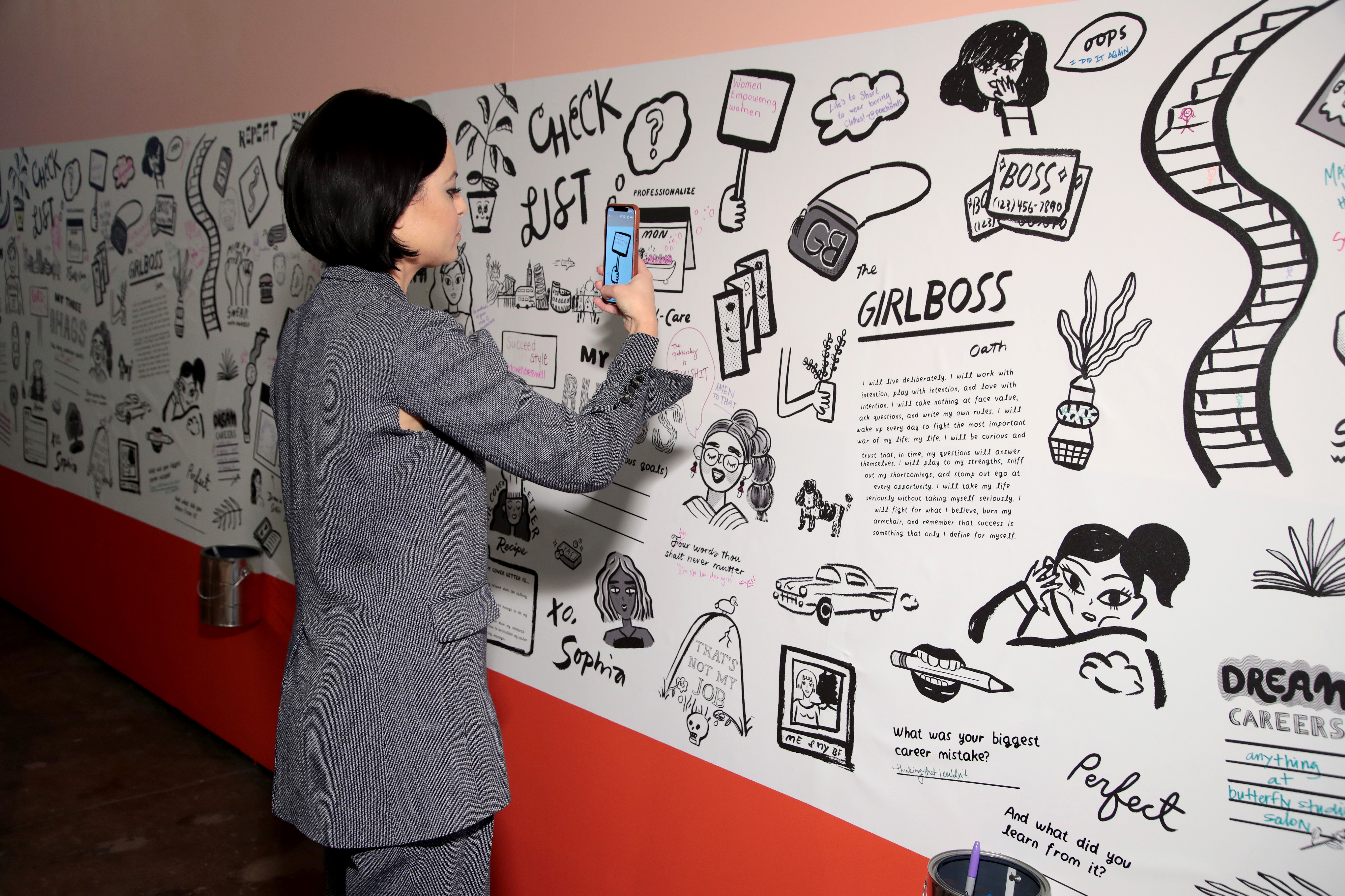 Girlboss founder Sophia Amoruso takes a close-up picture with her phone of a wall mural at a Girlboss rally.