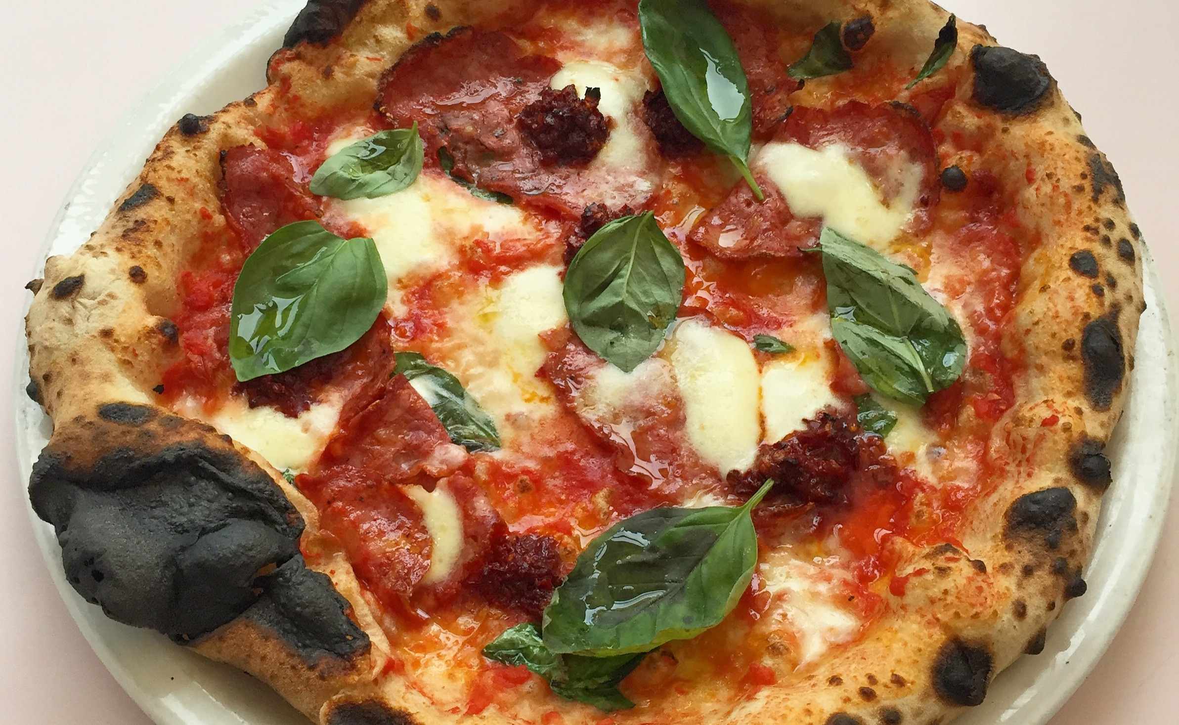 Sourdough pizza with tomato, mozzarella, basil, and 'nduja sausage at Theo's Pizzeria in Camberwell, one of the best restaurants in Camberwell, south London