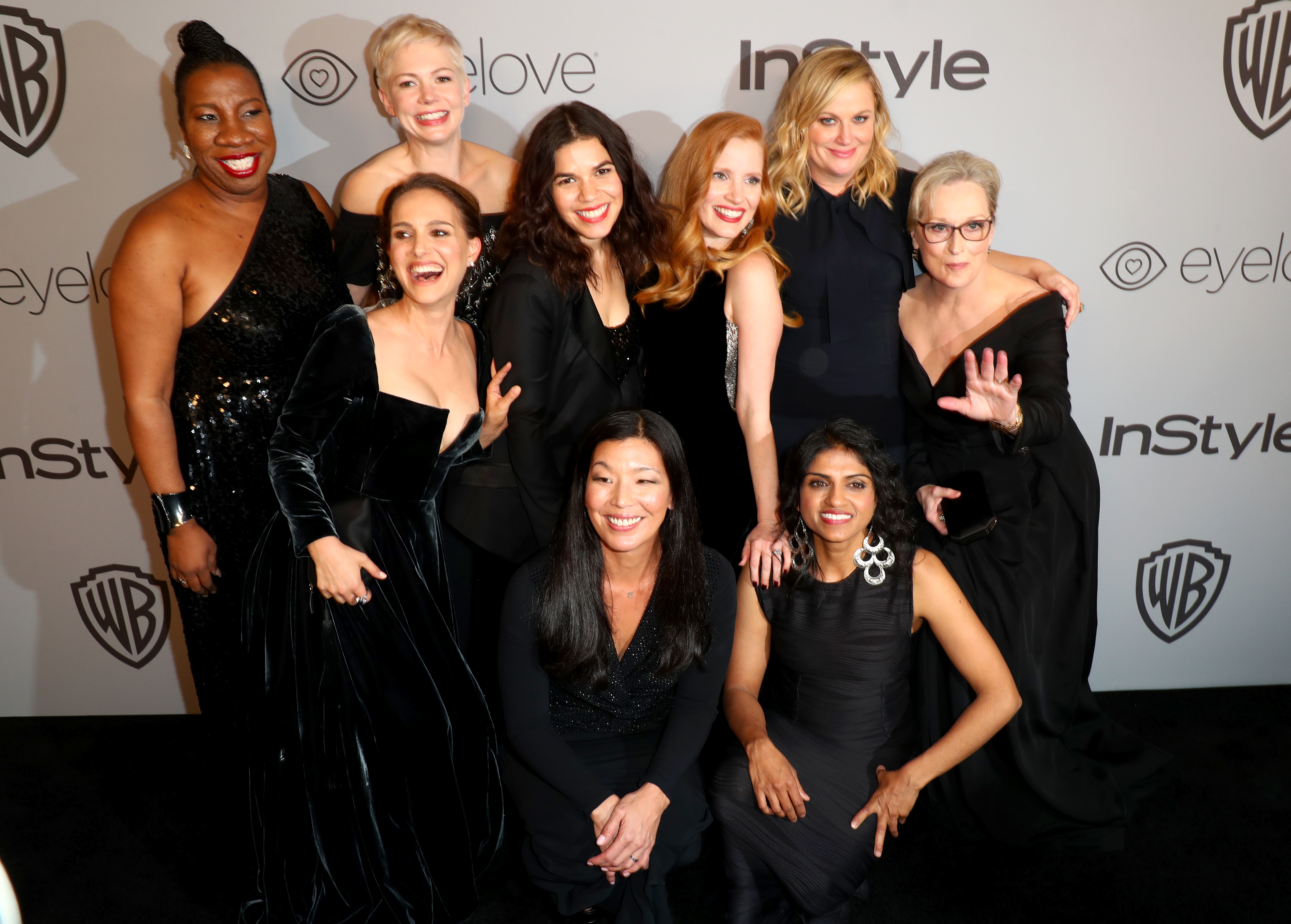The women stand in a huddle, smiling at the camera, all wearing black.