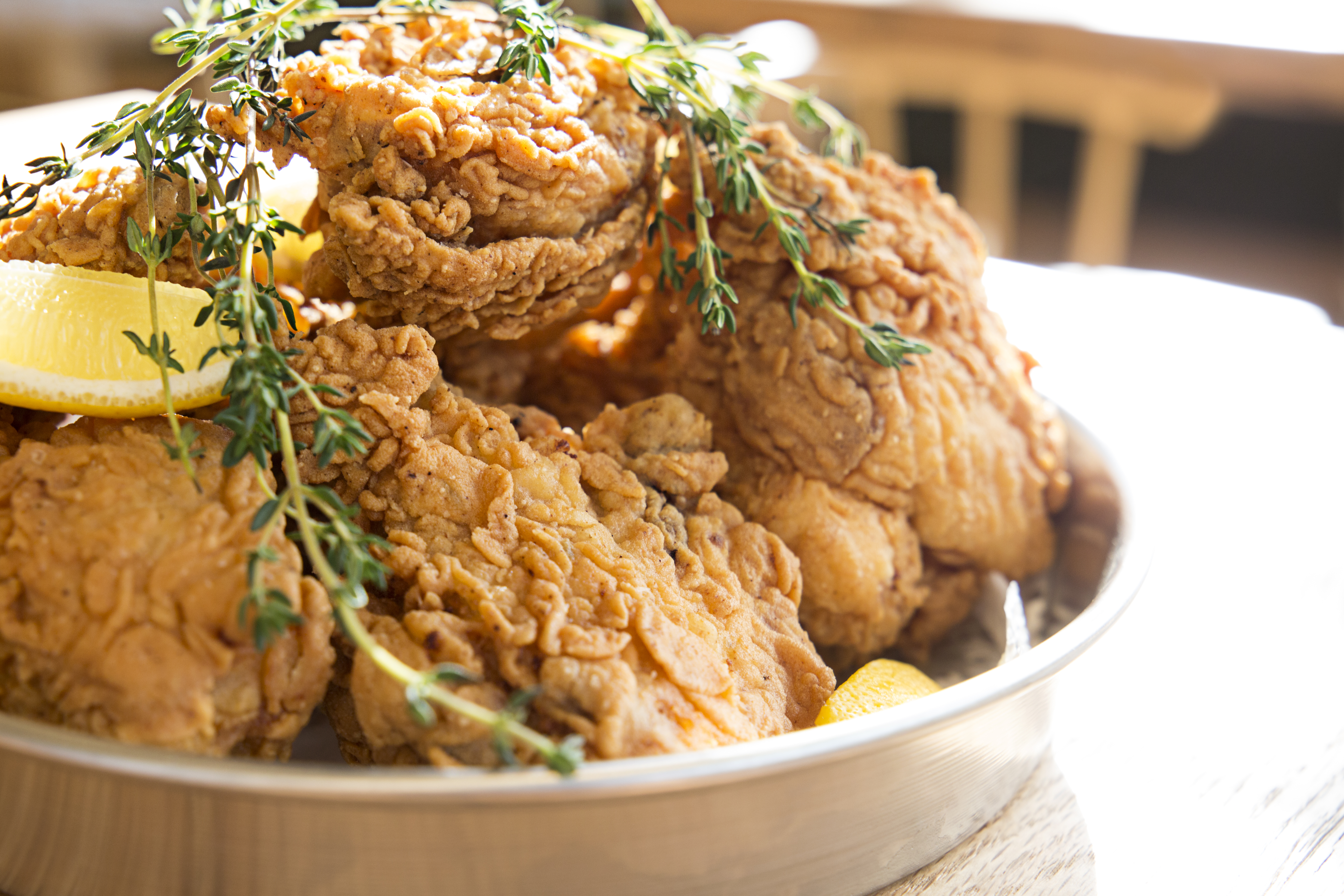 A plate of fried chicken from Southern Proper, a restaurant in Boston's South End neighborhood. The chicken is adorned with sprigs of thyme and lemon wedges, and is served in a pie tin.