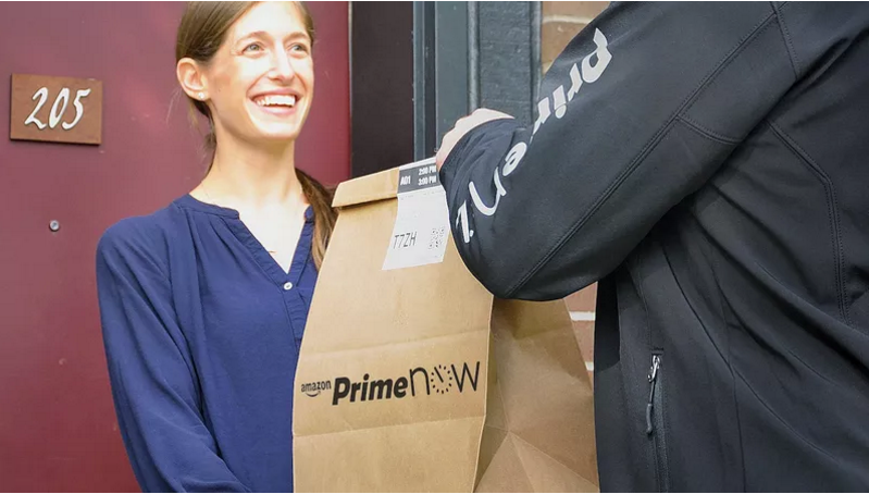an amazon prime now delivery person hands a bag to a customer