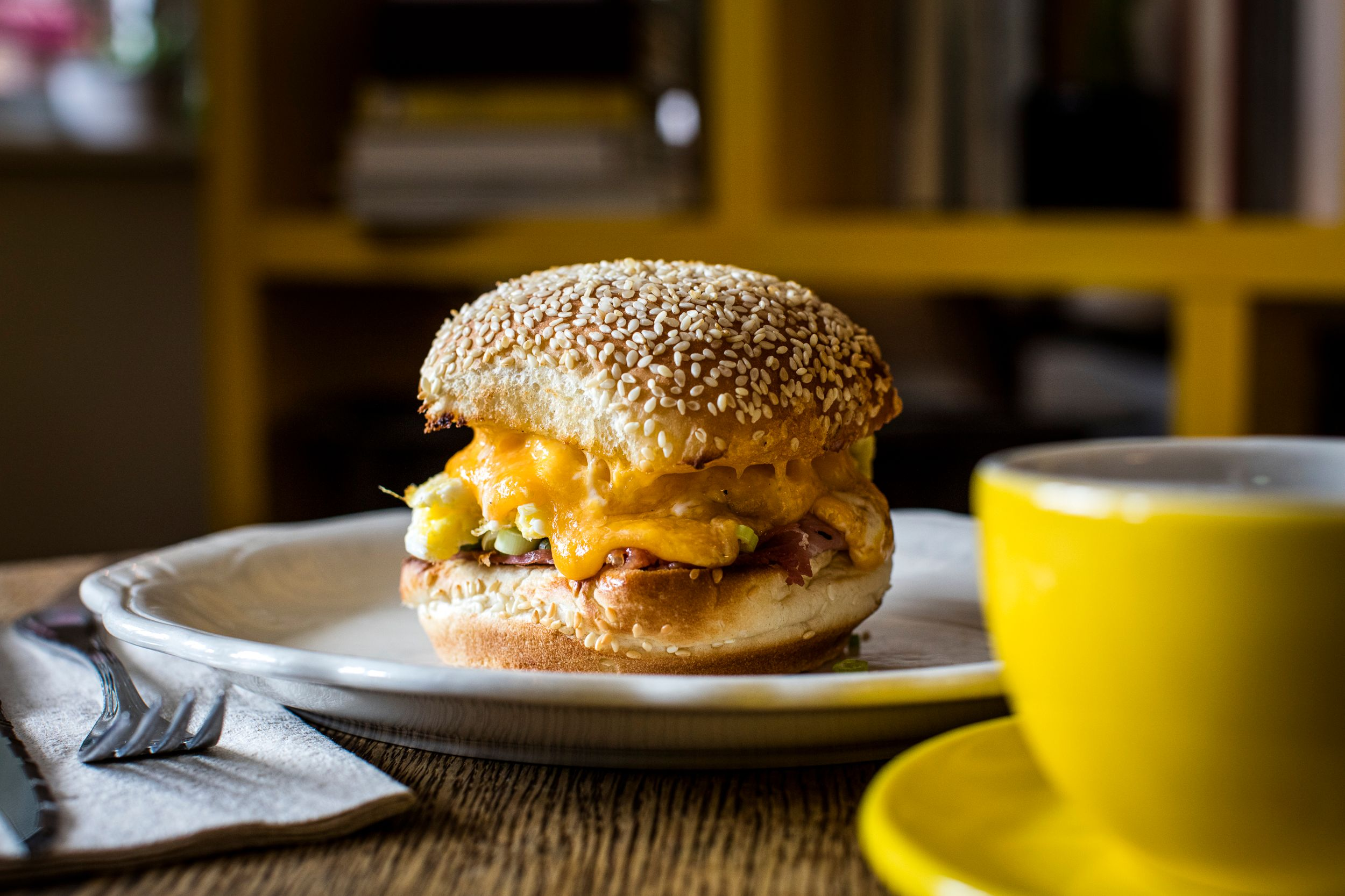A close-up shot of a cheesy egg sandwich on a sesame seed bun with a yellow mug of coffee in the foreground.