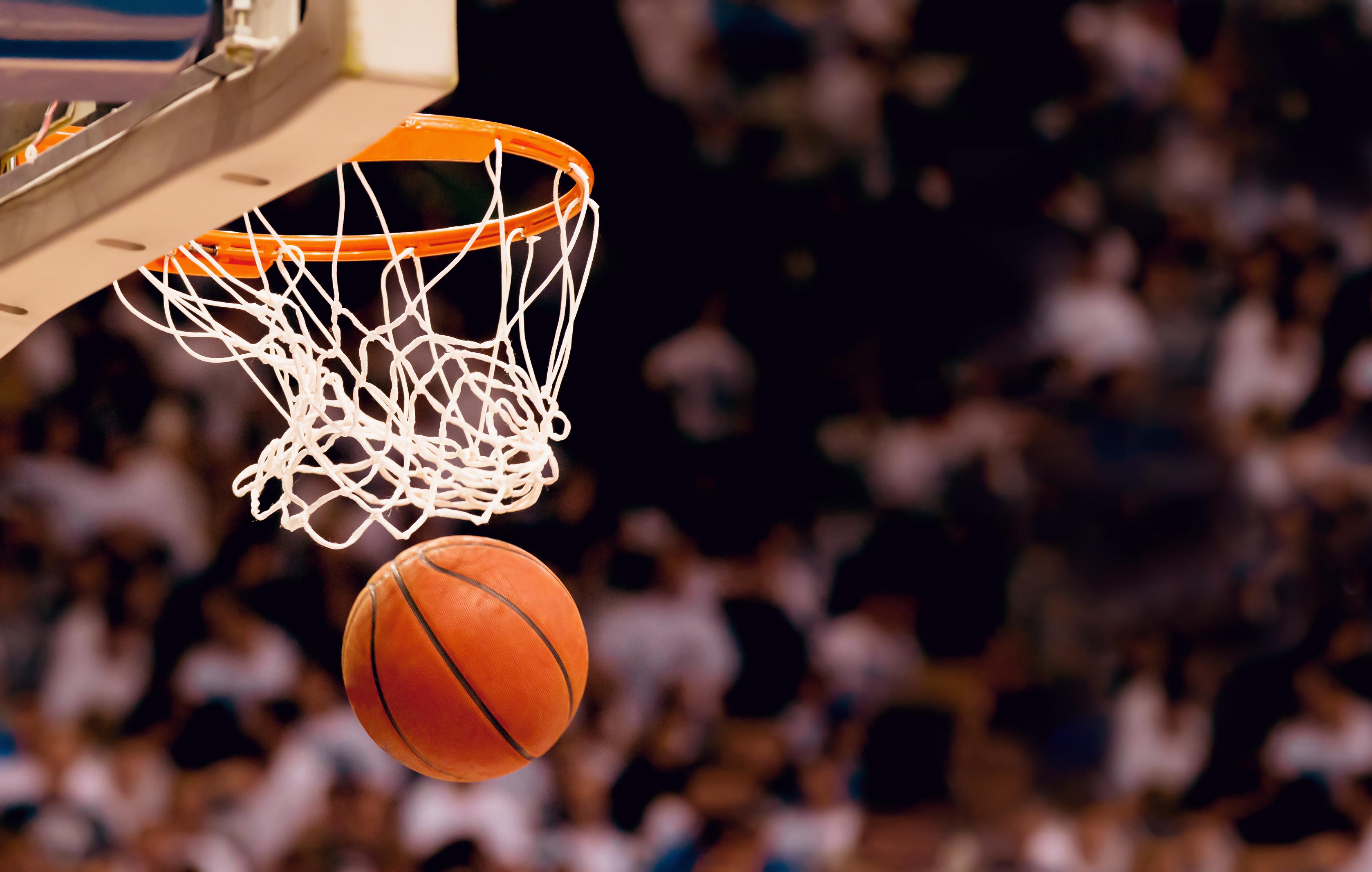 stock image of a basketball going through a hoop