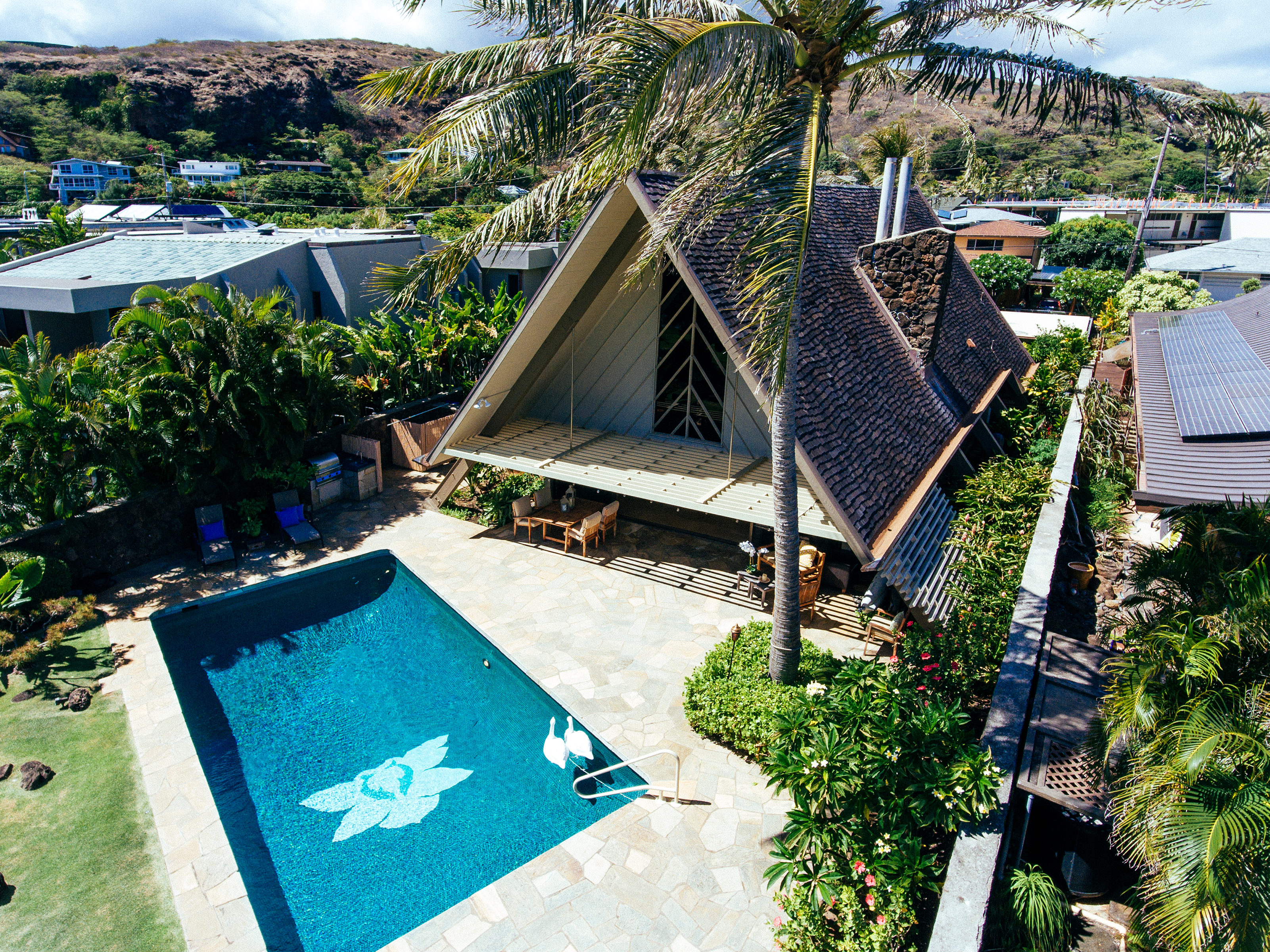 A-frame house with pool in tropical setting.