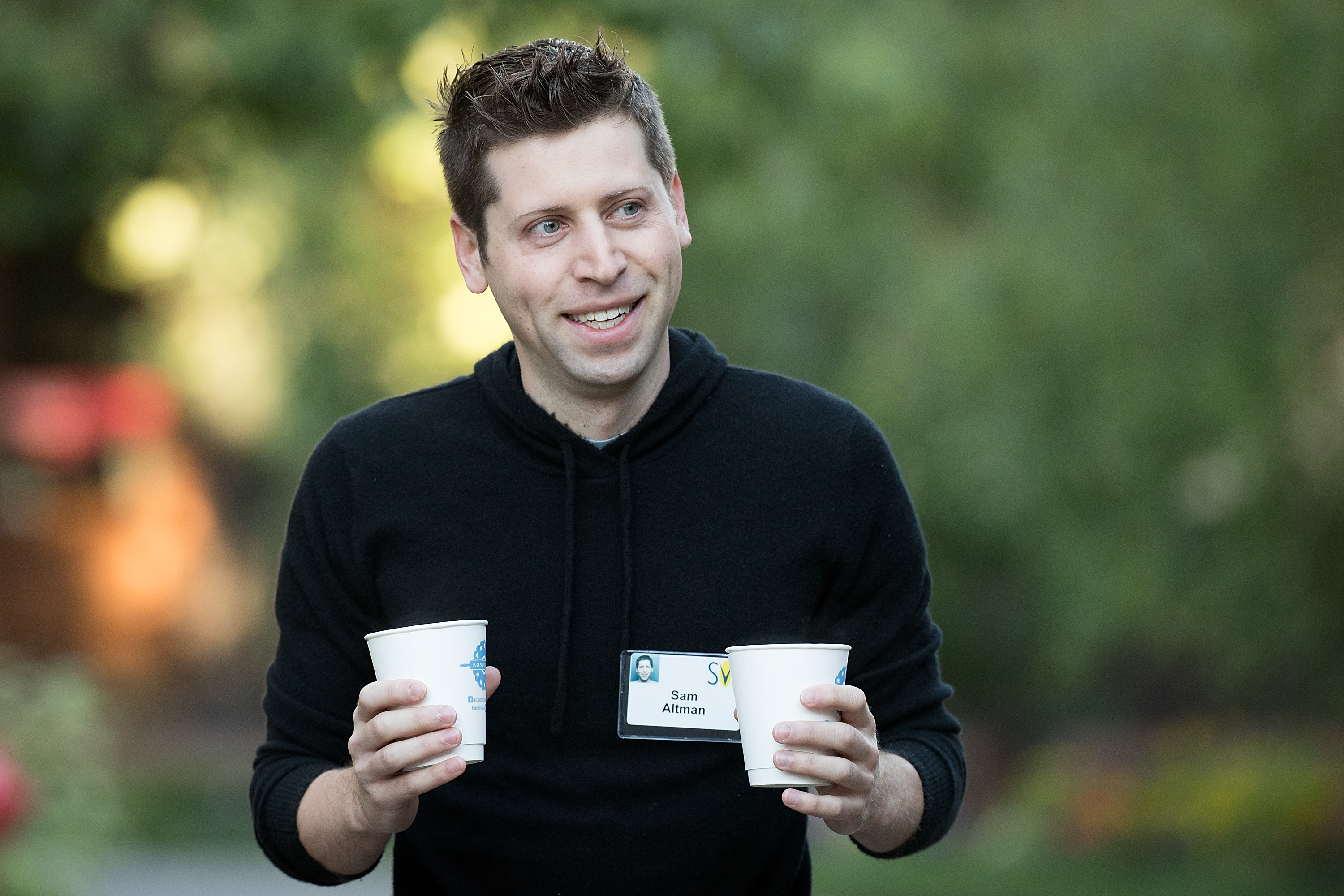 Y Combinator President Sam Altman holding two paper cups of coffee