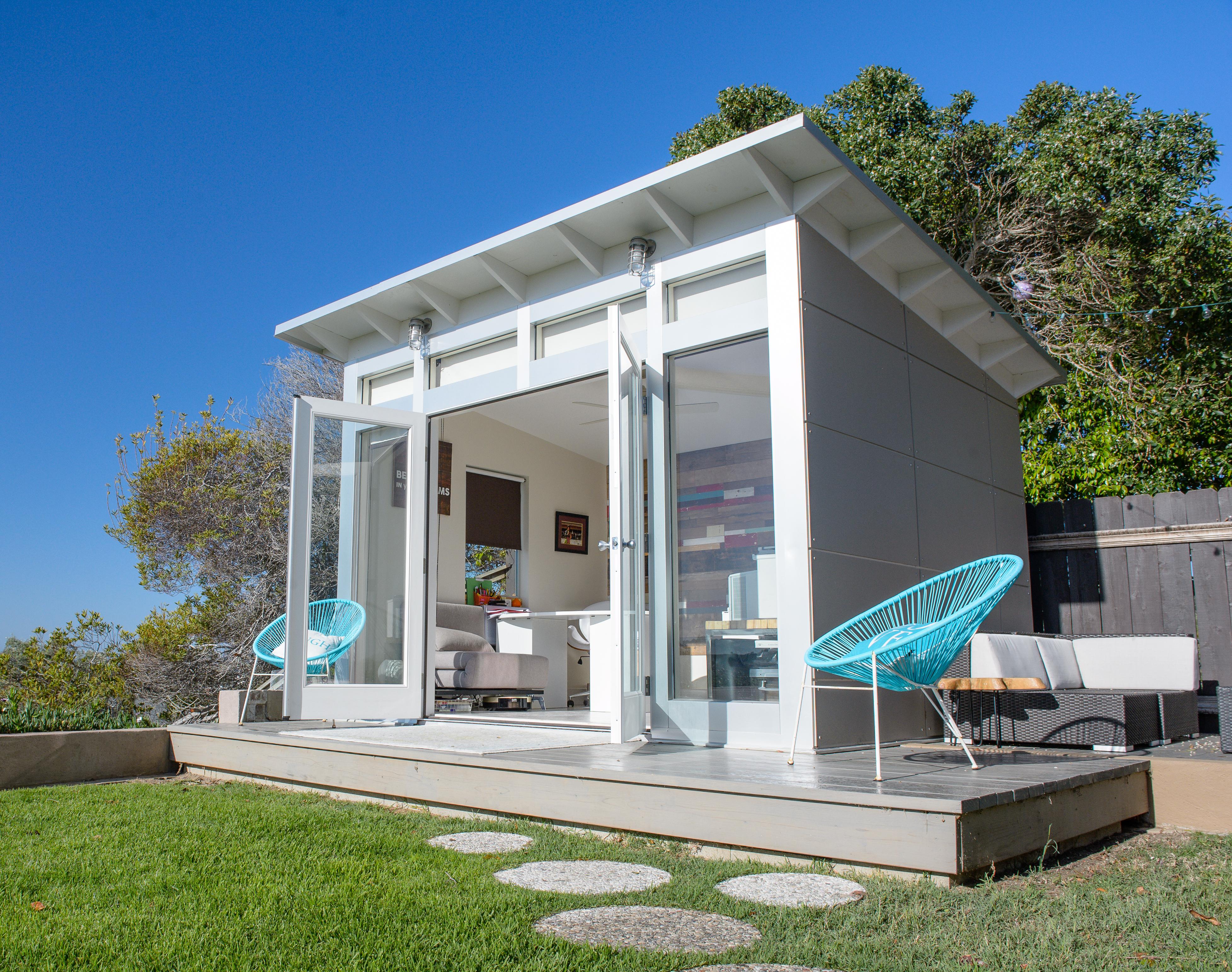 A boxy modern office shed on a platform.