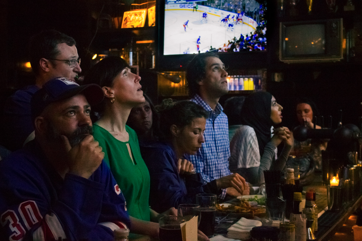 Patrons watch a sports game in a bar