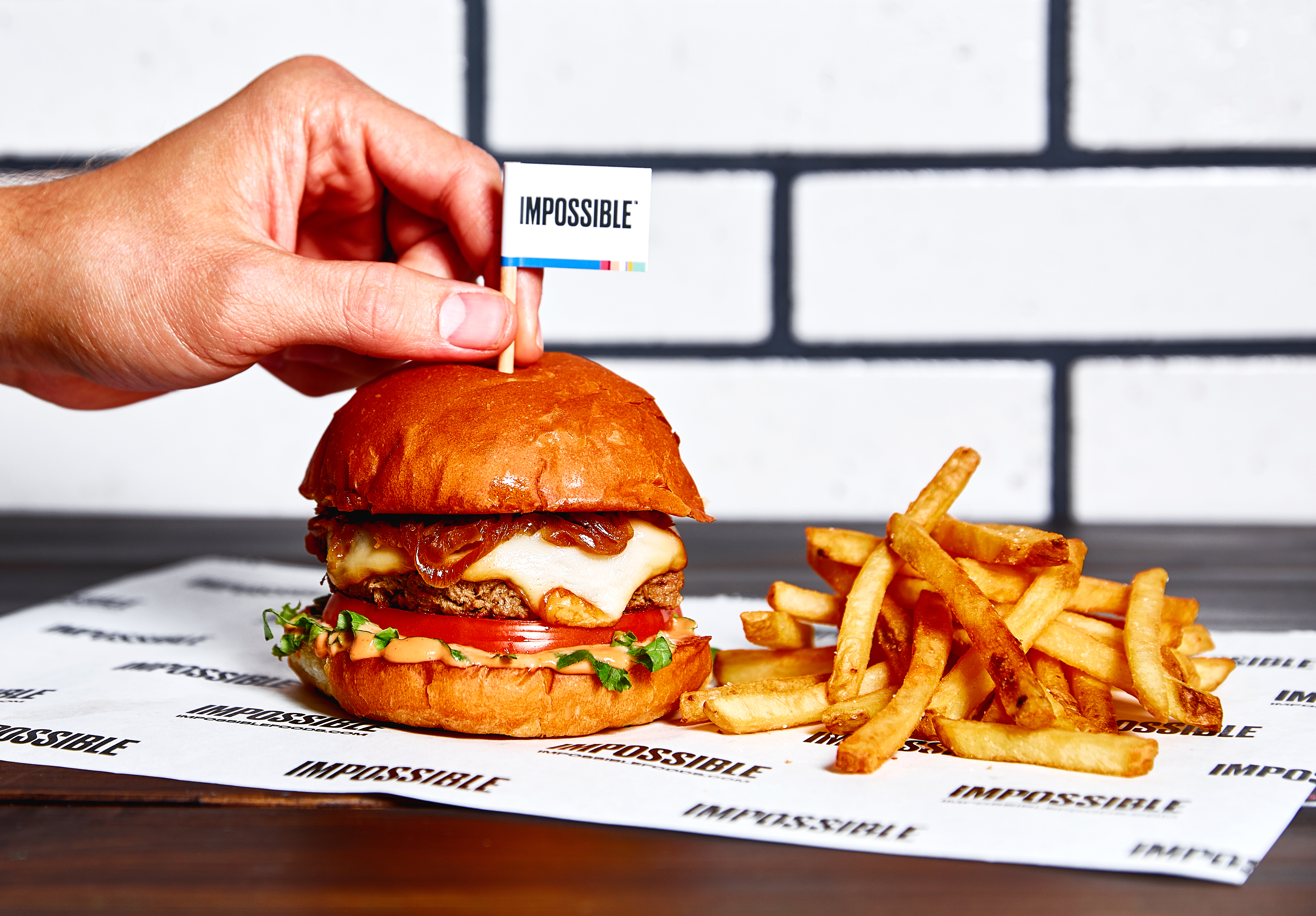 """A hand sticks a toothpick flag that reads """"Impossible"""" in a bun atop the Impossible Burger at Wahlburgers"""
