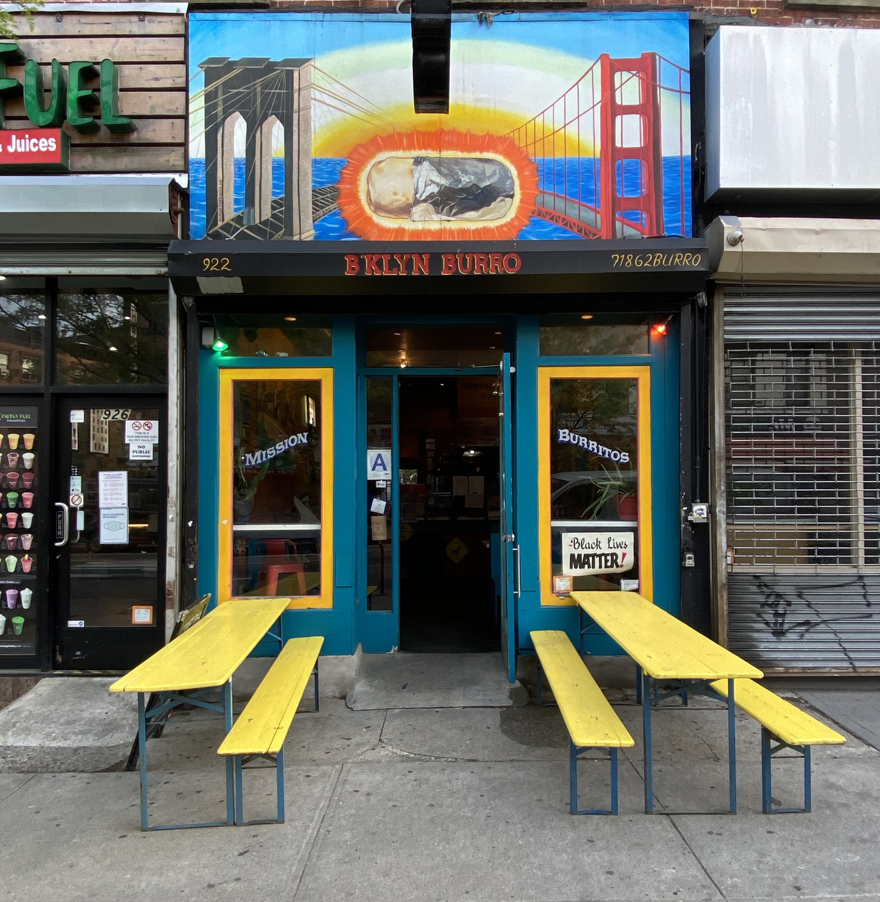 A colorful restaurant with two yellow picnic tables out front and a painted mural of the San Francisco Bridge.