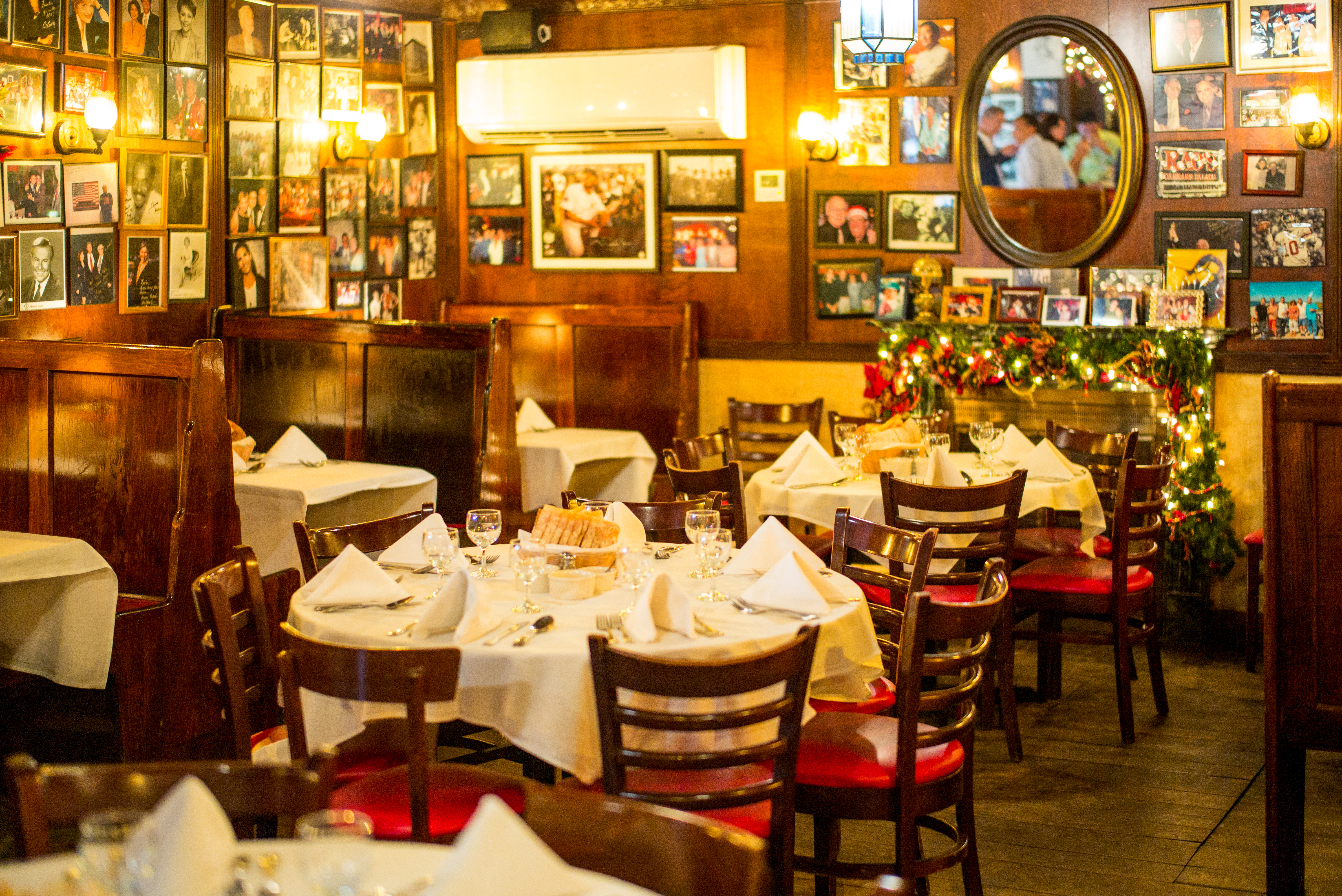The dining room of a restaurant with white table cloth lined tables, black chairs, and a plethora of photos on the wall