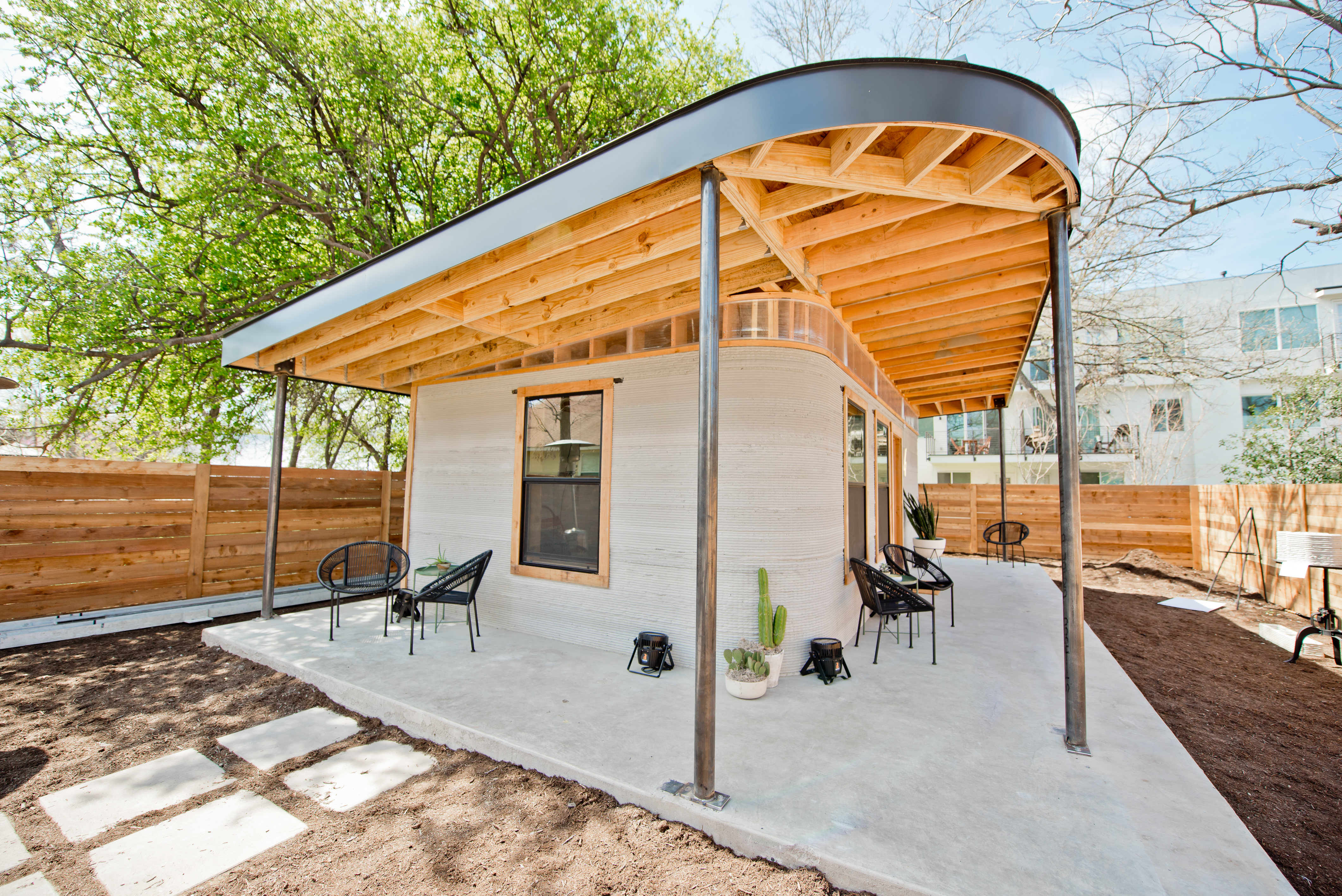 Small cement home with rounded front corner and covered wraparound porch