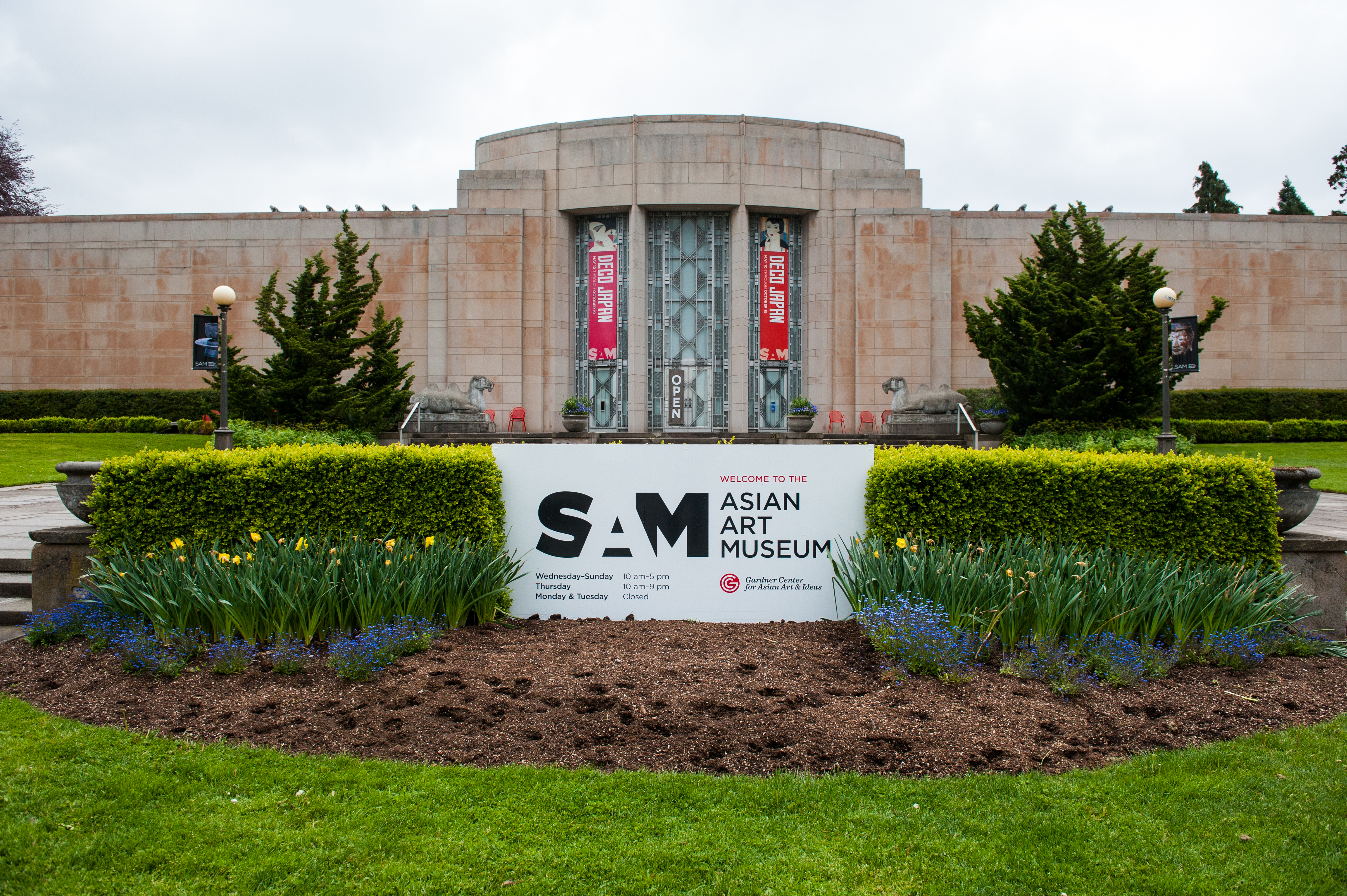 """A stone, Art Deco building with a central, rounded bay with three vertical stained-glass windows. There's landscaping in the front around a sign that says """"SAM ASIAN ART MUSEUM."""""""