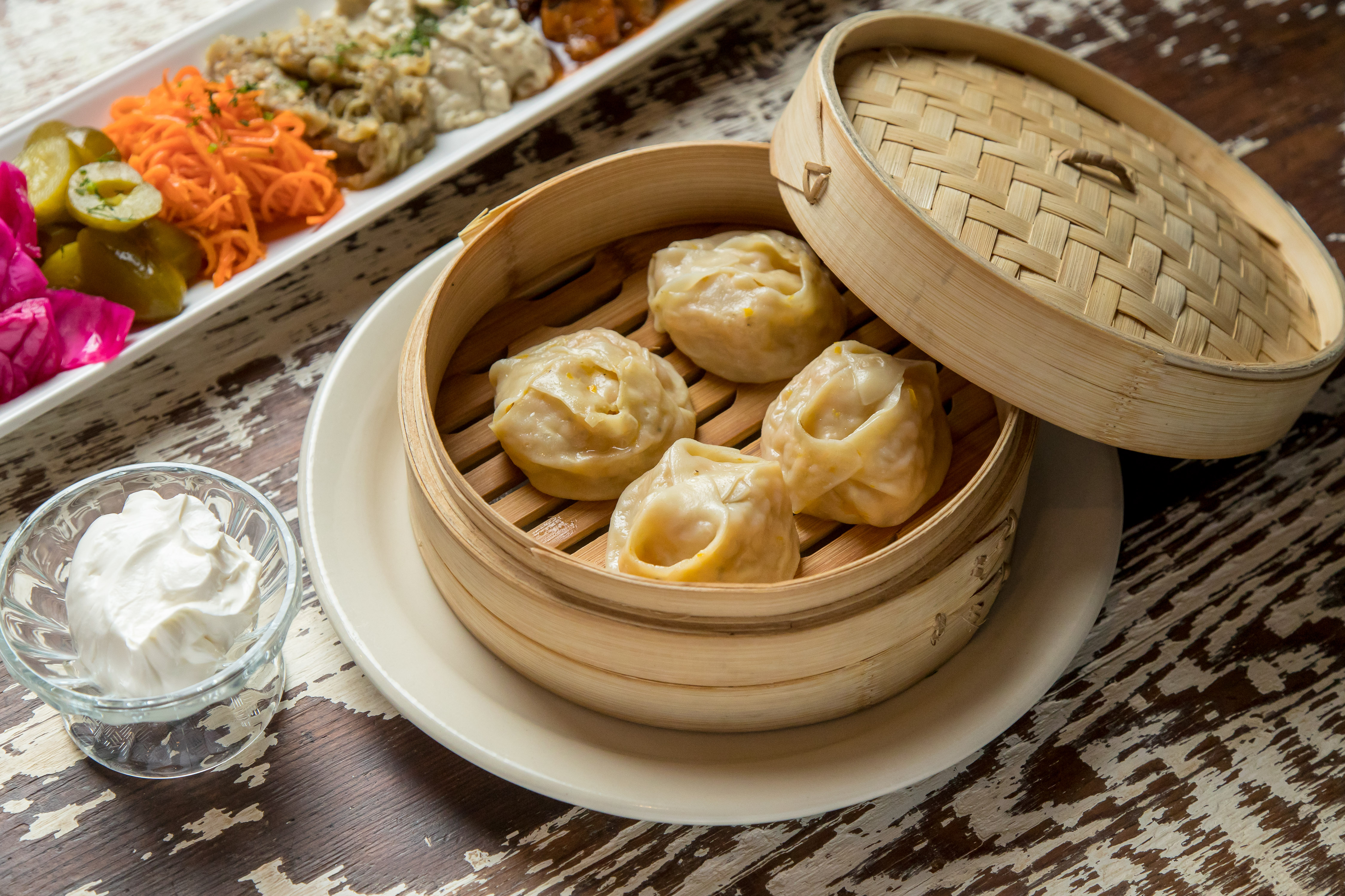Dumplings in a bamboo container, with the lid half-off
