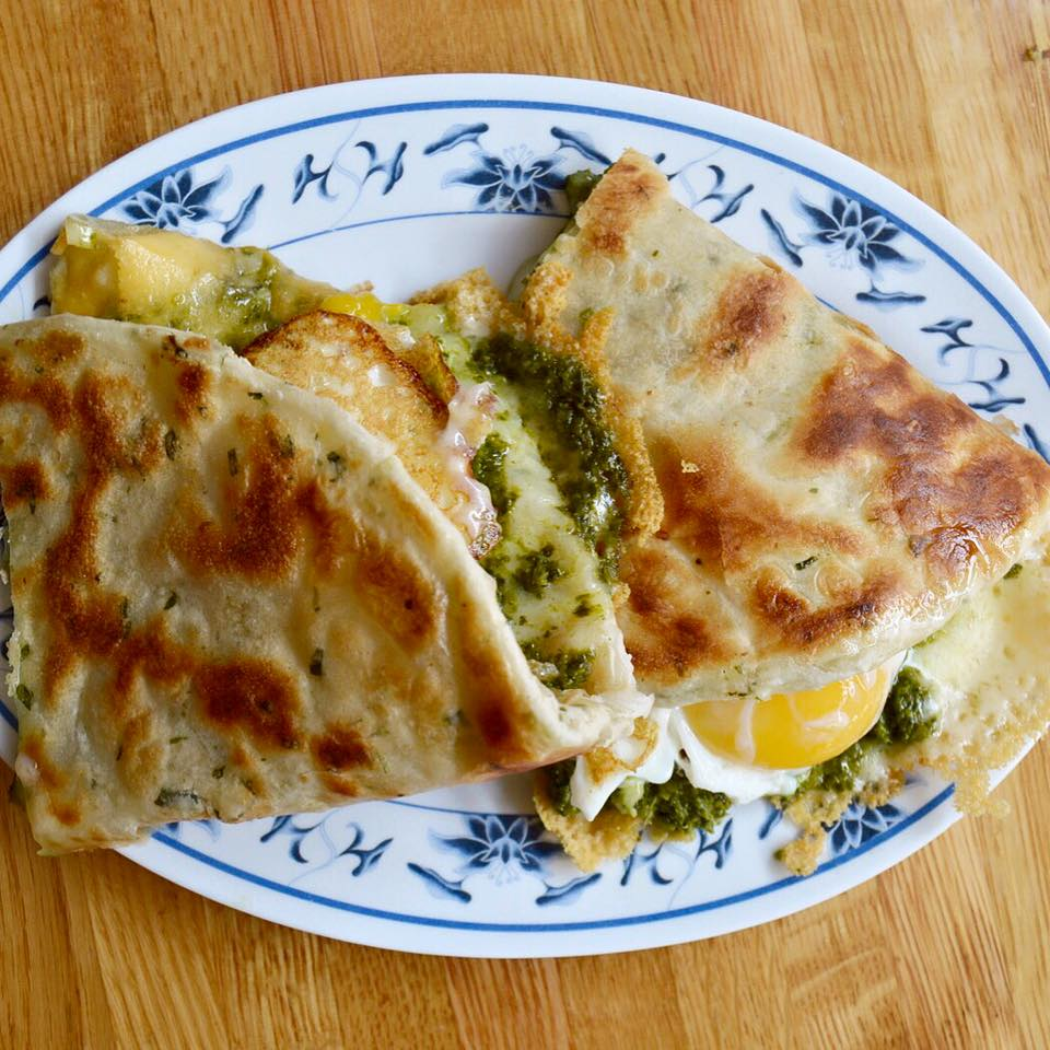 """scallion pancake """"sandwich"""" stuffed with greens and oozy eggs on a white plate with a blue floral border"""