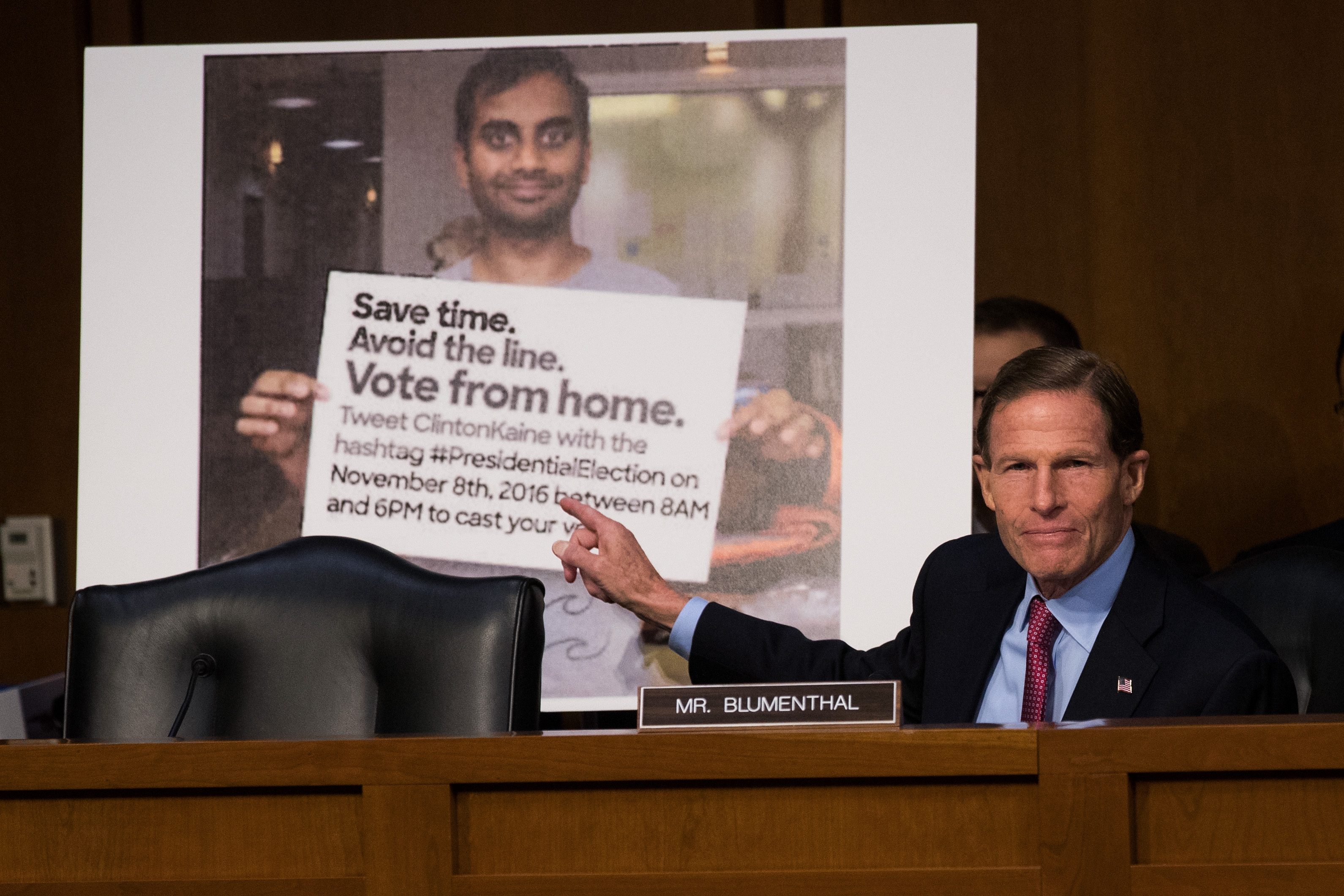 With a Twitter post encouraging voters to vote from home displayed behind him, Sen. Richard Blumenthal (D-CT) questions witnesses during a Senate hearing on Russian disinformation.