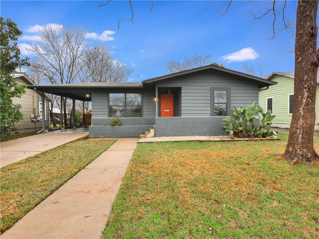Photo of a remodeled 1950s home with gray walls and red door