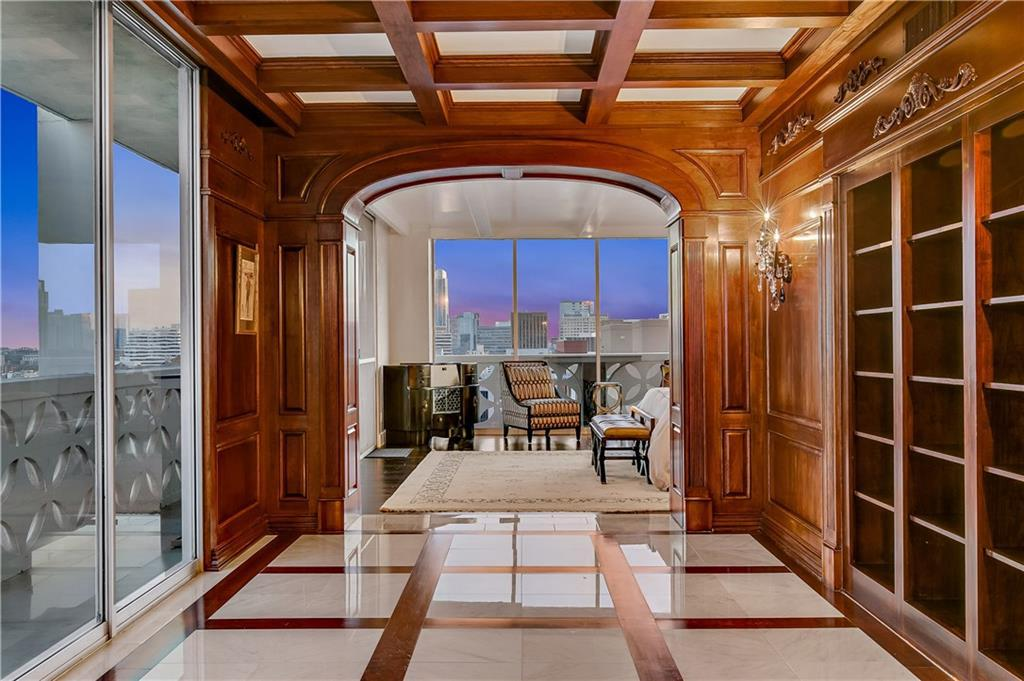Wide hallway with balcony on left, wood ceiling and built-in shelves on right, and marble floor