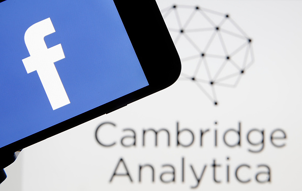 The Facebook logo is seen on the screen of an iPhone in front of a computer screen showing a Cambrige Analytica logo on March 20, 2018 in Paris, France. Cambridge Analytica is accused of collecting the personal data of 50 million users of the Facebook soc