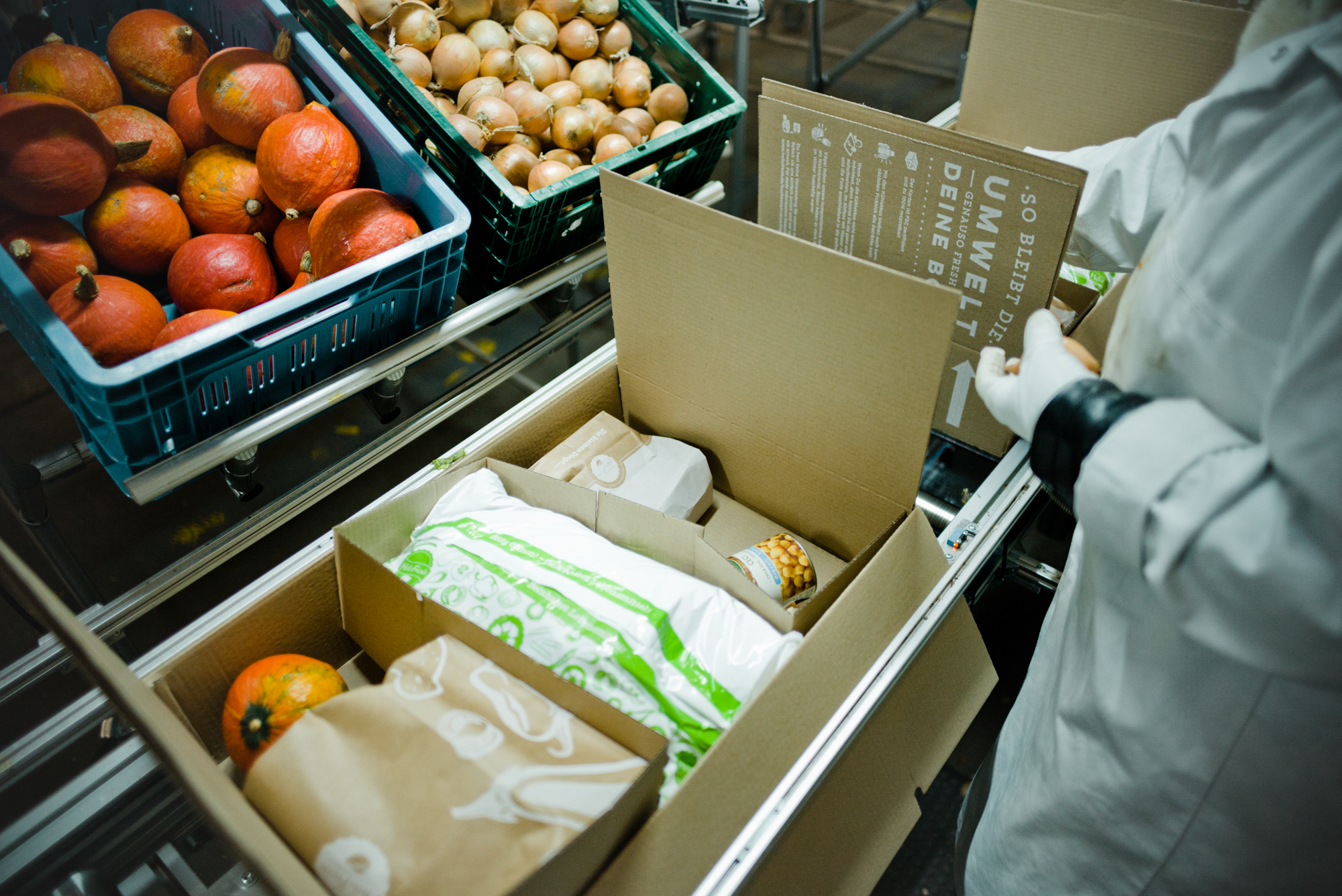 A worker packing a HelloFresh box with food