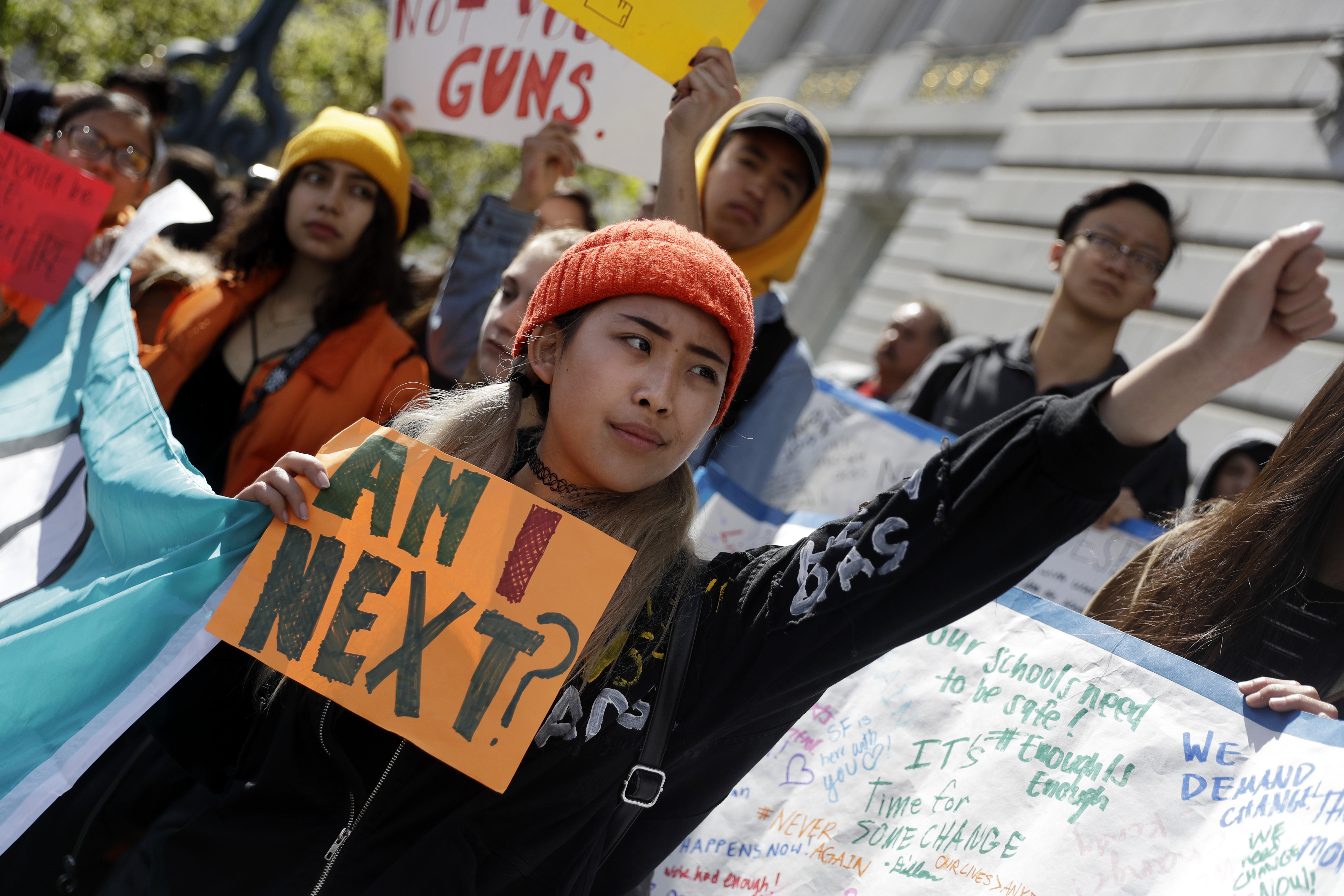 Sandy Shieh, a student at San Francisco's Lincoln High School, holds a sign during a rally and march against gun violence at the Civic Center Plaza.