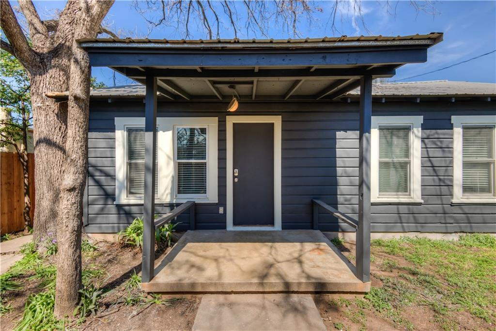 Small home with flat roof painted dark gray, covered sidewalk