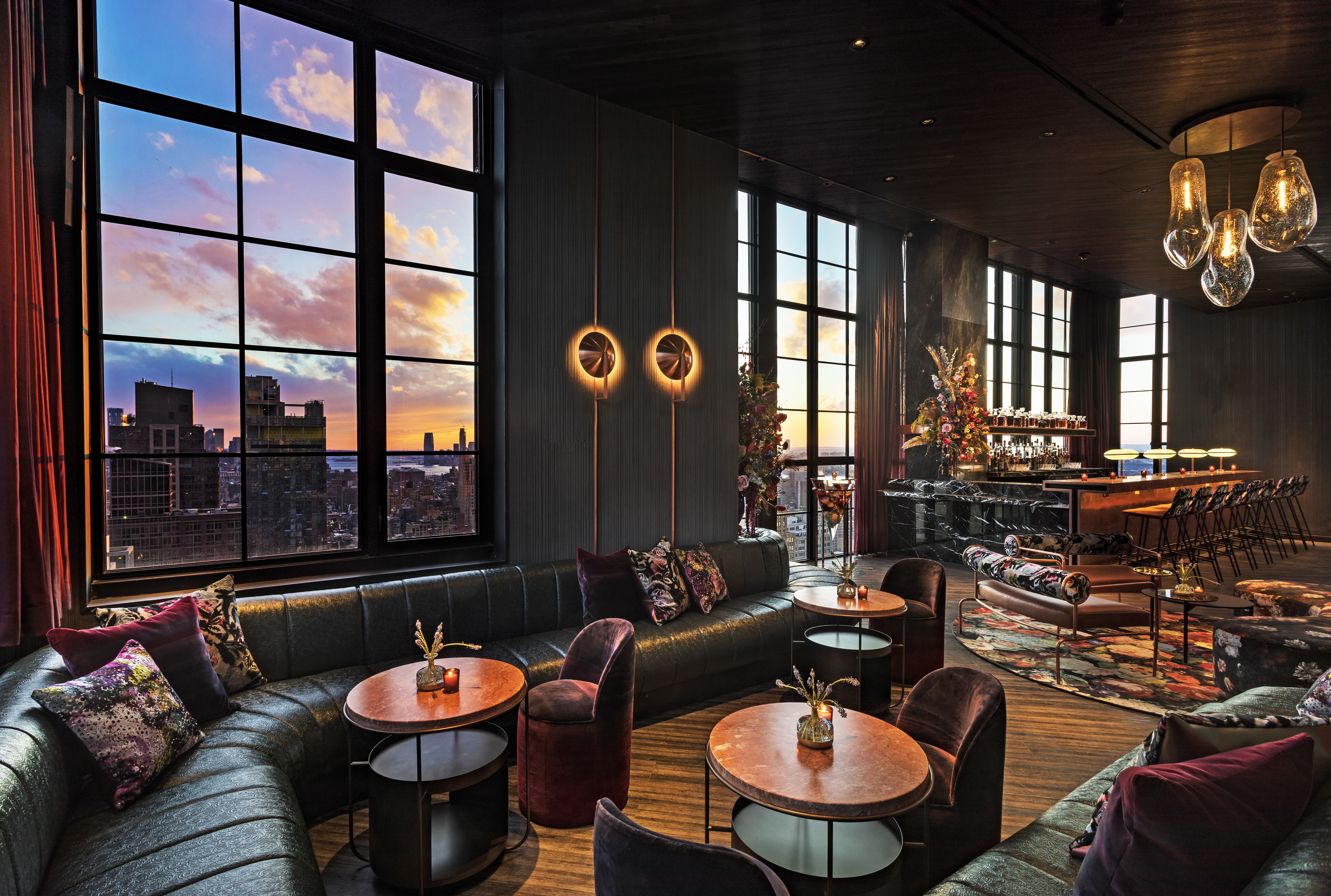 The interior of a hotel restaurant. There are tables and seating. Large windows overlook city buildings and a colorful sunset.