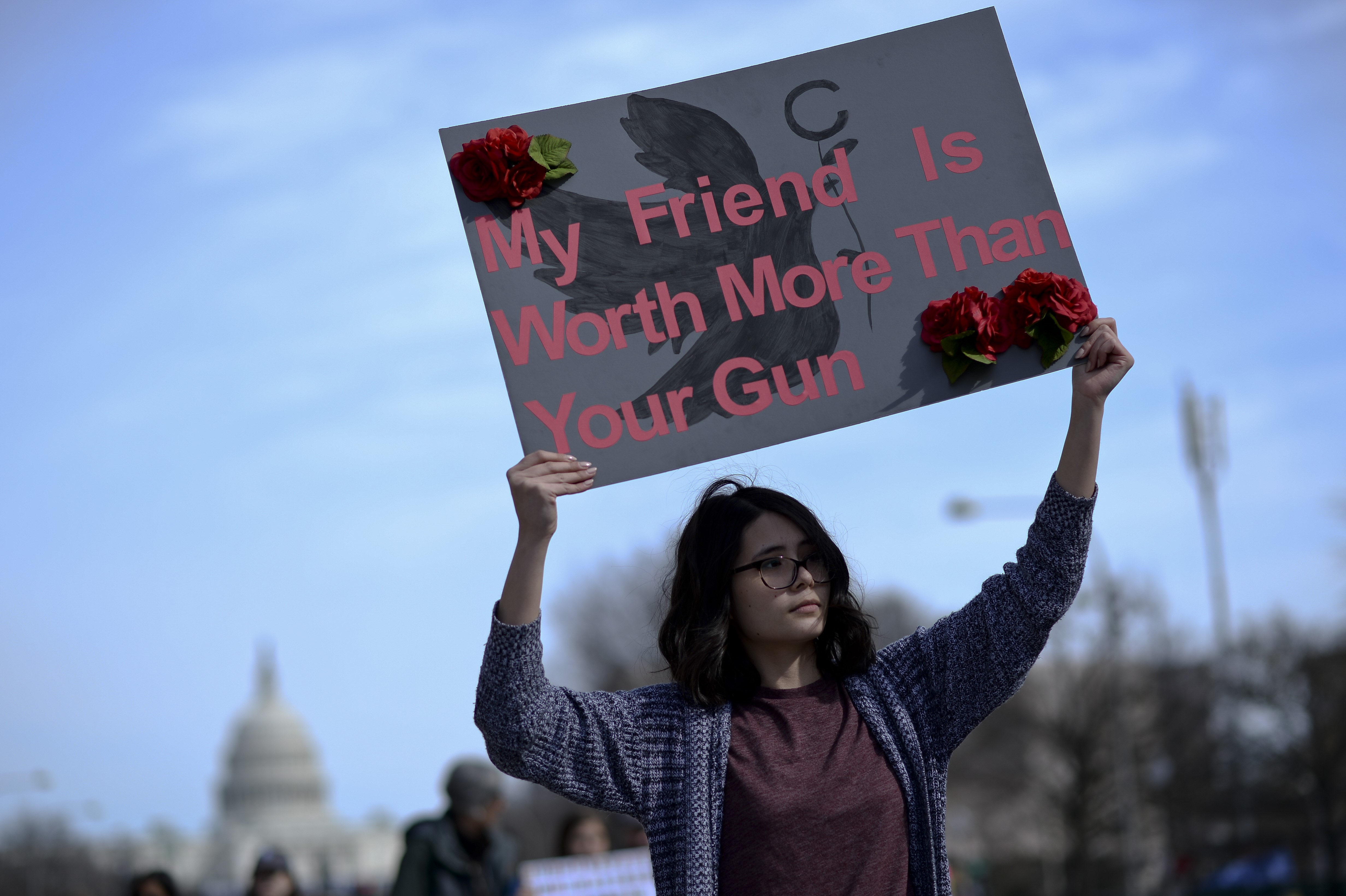 """A young woman carries a sign saying """"My friend's life is worth more than your gun."""""""