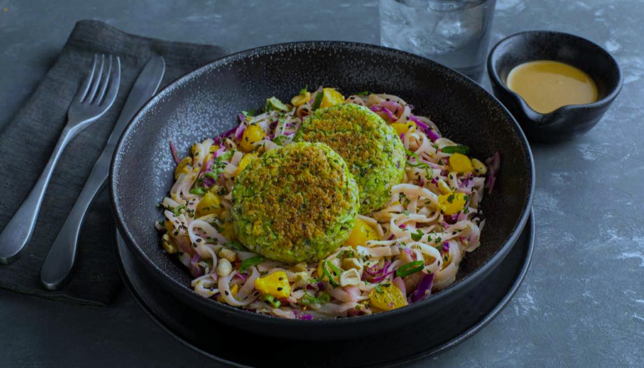 Edamame falafel patties on rice noodle salad in a black serving dish
