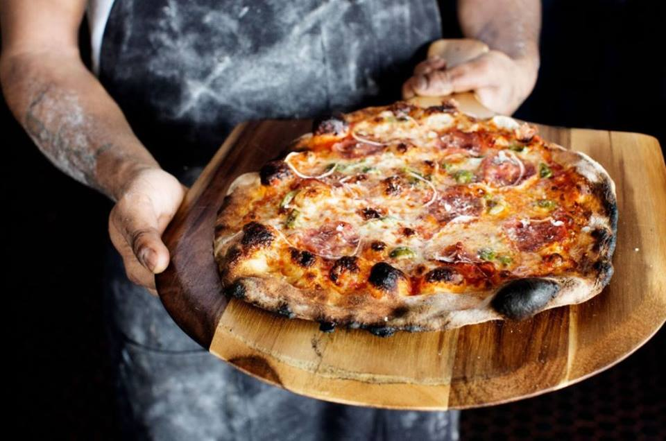 A flour-covered chef presents a blistered crust with cheese and toppings