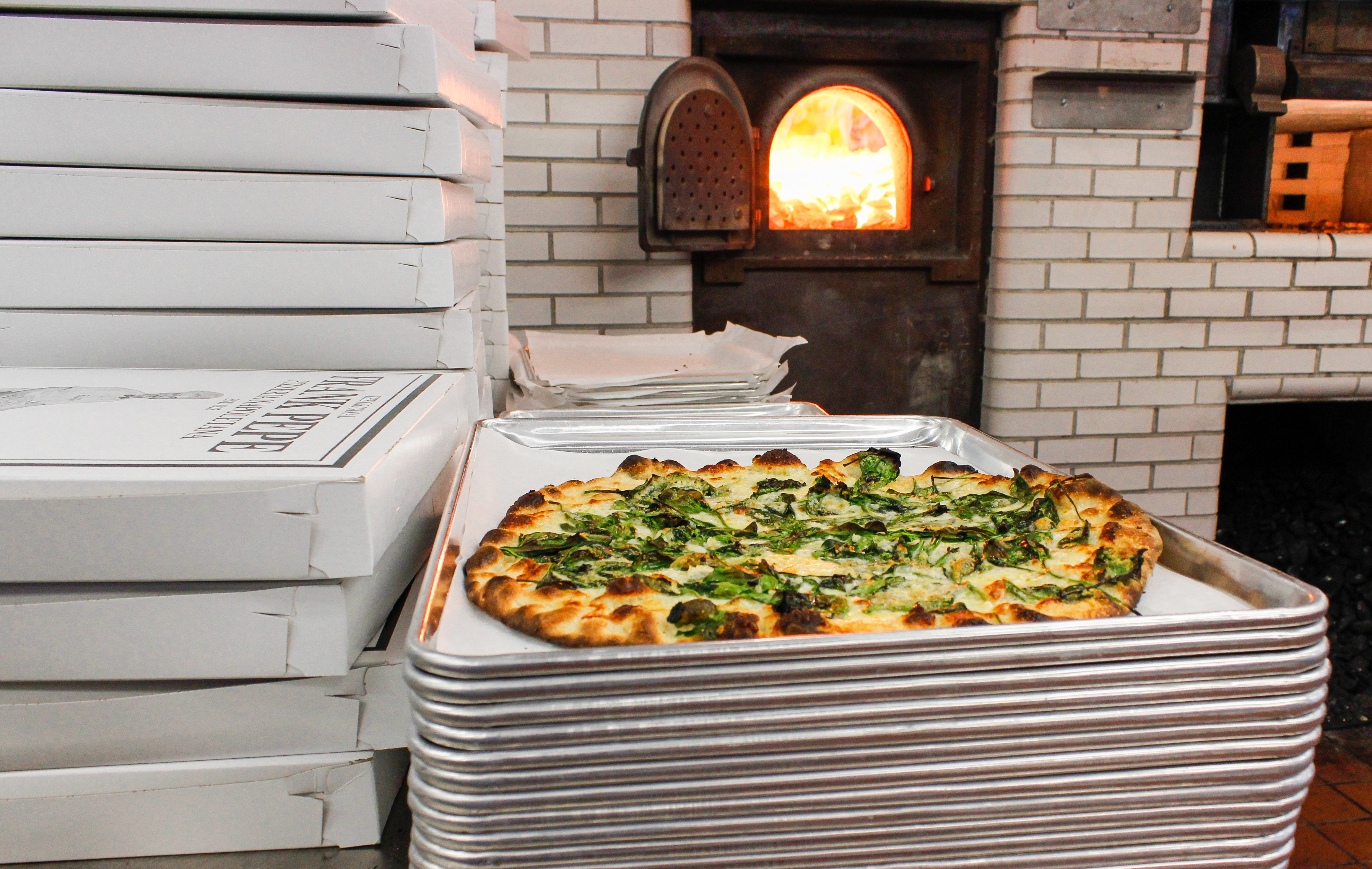 A New Haven-style pizza with a charred crust sits on a stack of metal trays, next to a stack of pizza boxes, in front of a lit pizza oven