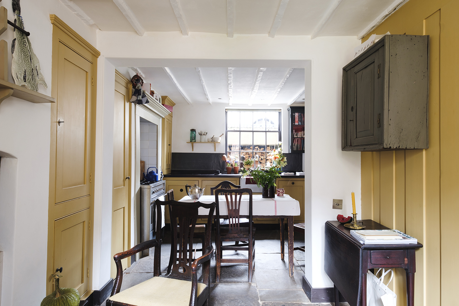 View of kitchen with ochre doors and paneling, white walls, and slightly exposed beams on the ceiling.