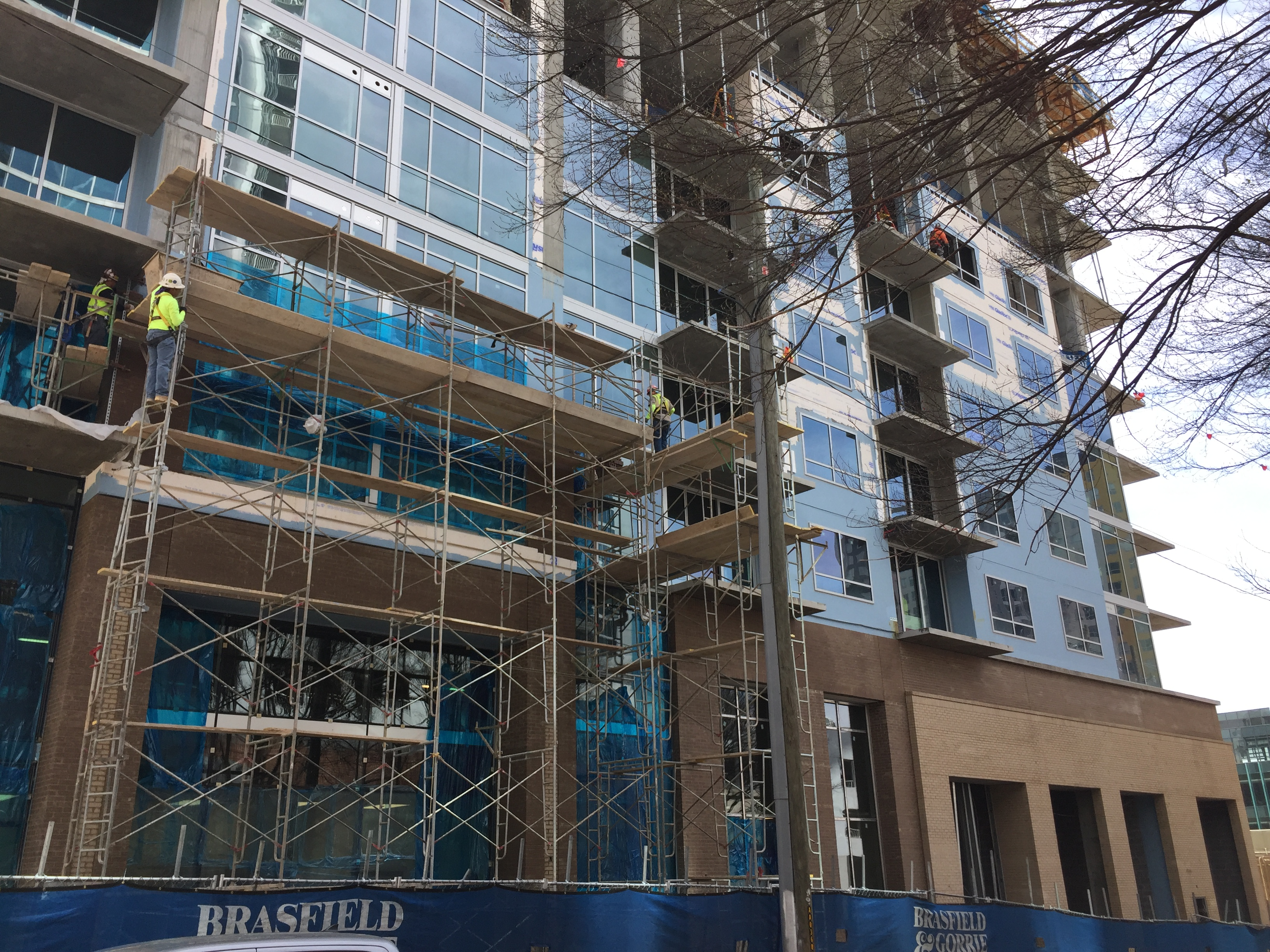 Brick is being applied to the base of the high-rise as work continues pouring the upper floors.