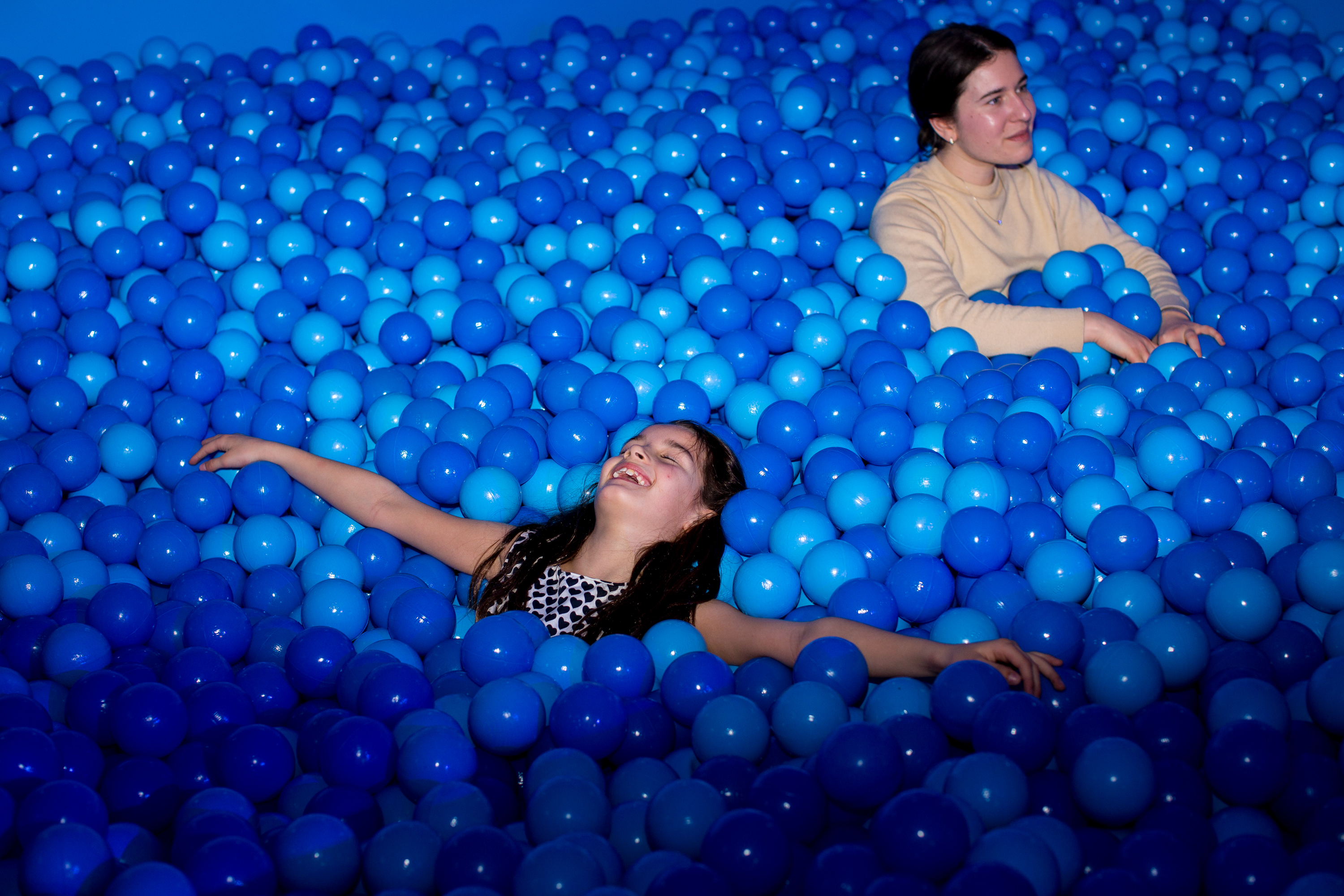 happy girl blue ball pit