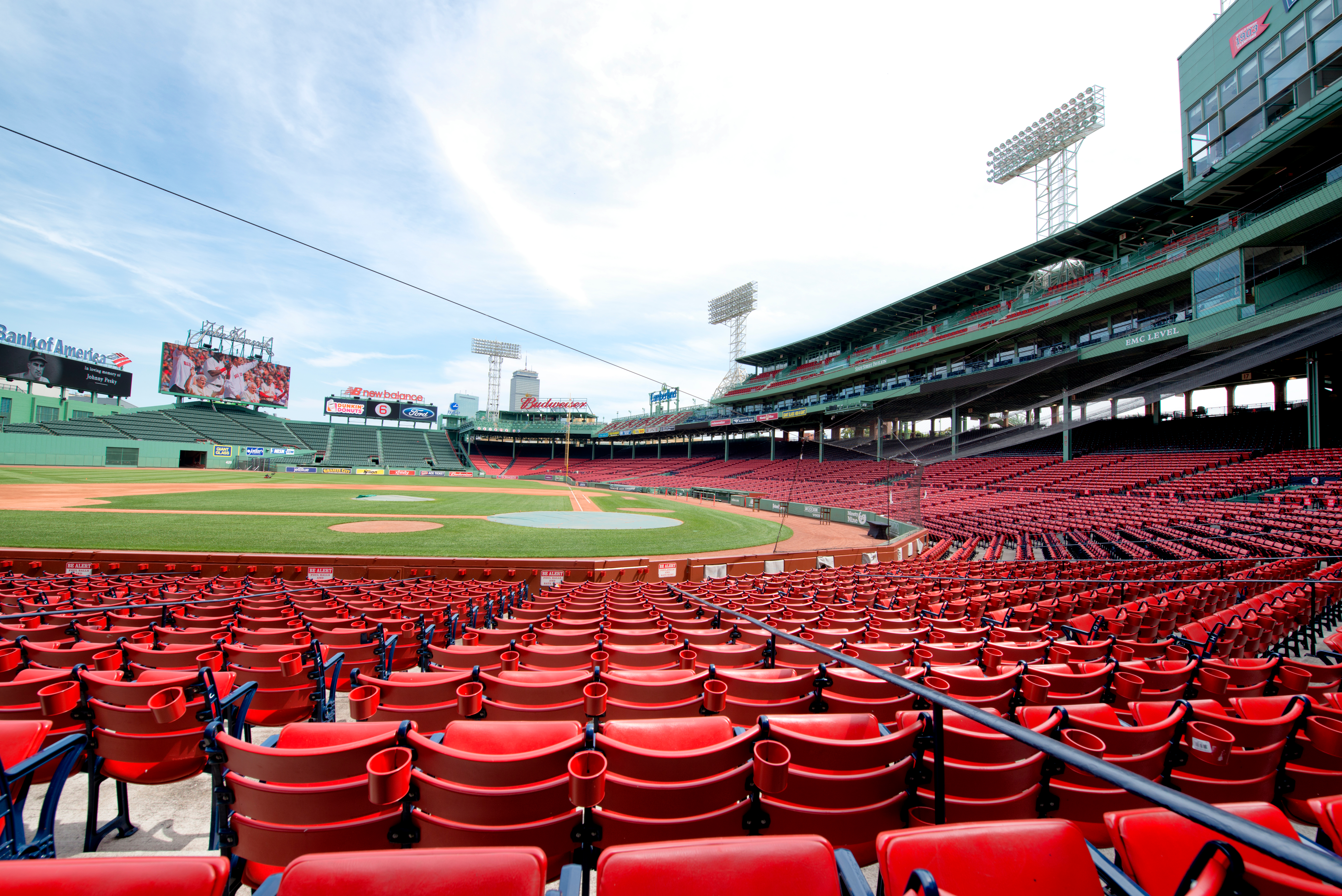Empty red seats at a large baseball arena.