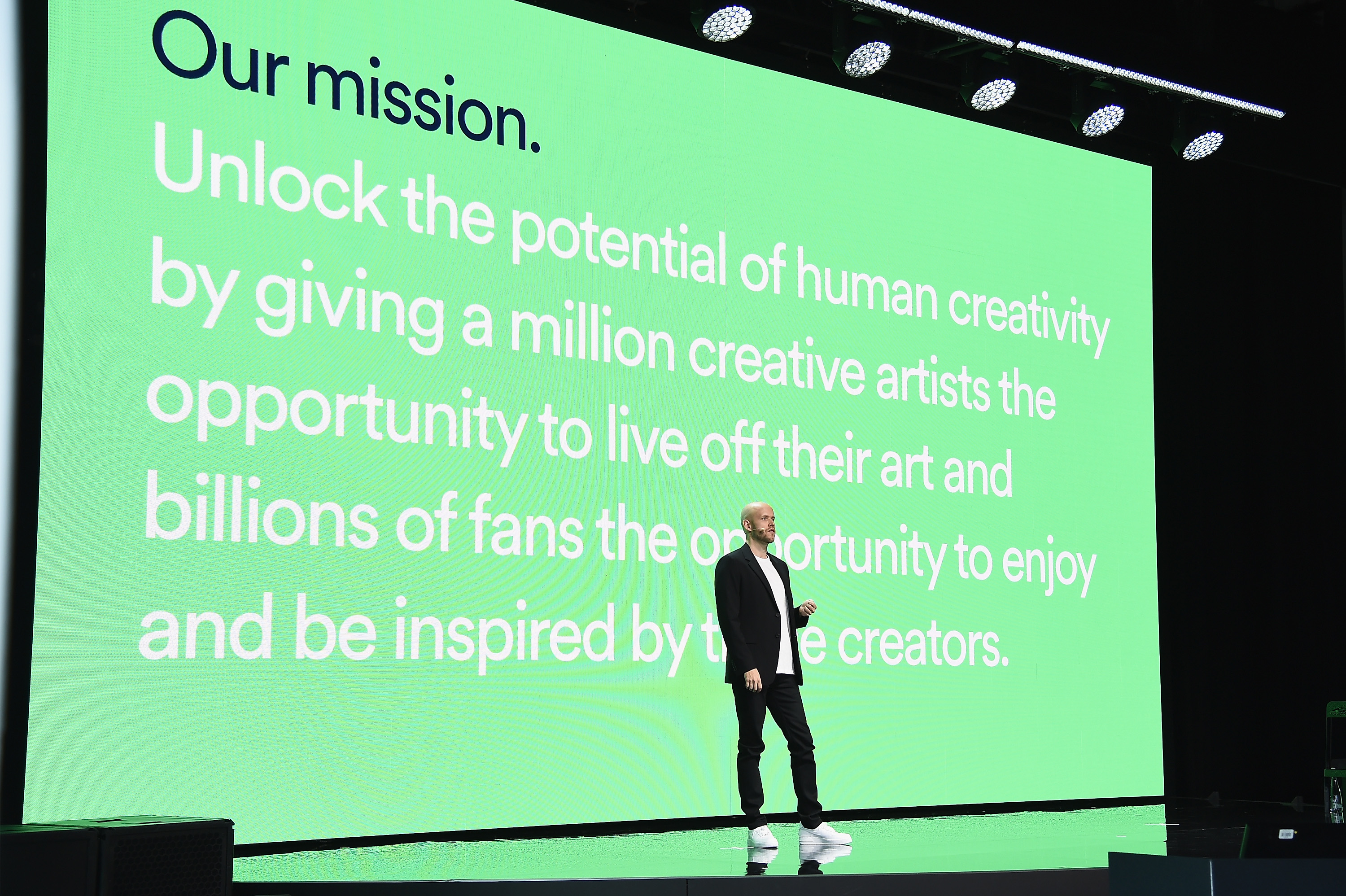 """Daniel Ek, founder and CEO of Spotify, speaks onstage during Spotify Investor Day in front of a screen that reads, """"Our mission: Unlock the potential of human capability by giving a million creative artists the opportunity to live off their art and billio"""