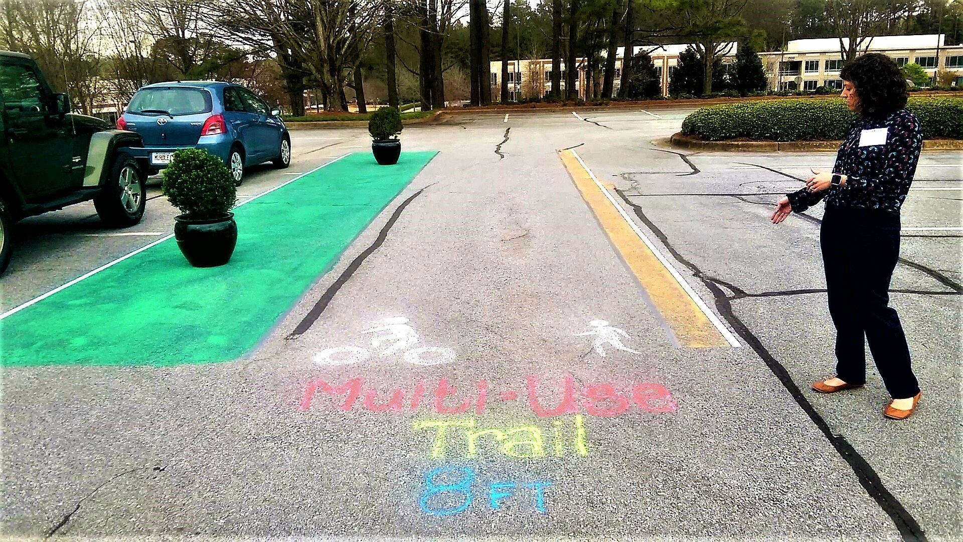 A woman in a parking lot points to a mocked-up version of a multi-use trail drawn with chalk and paint.
