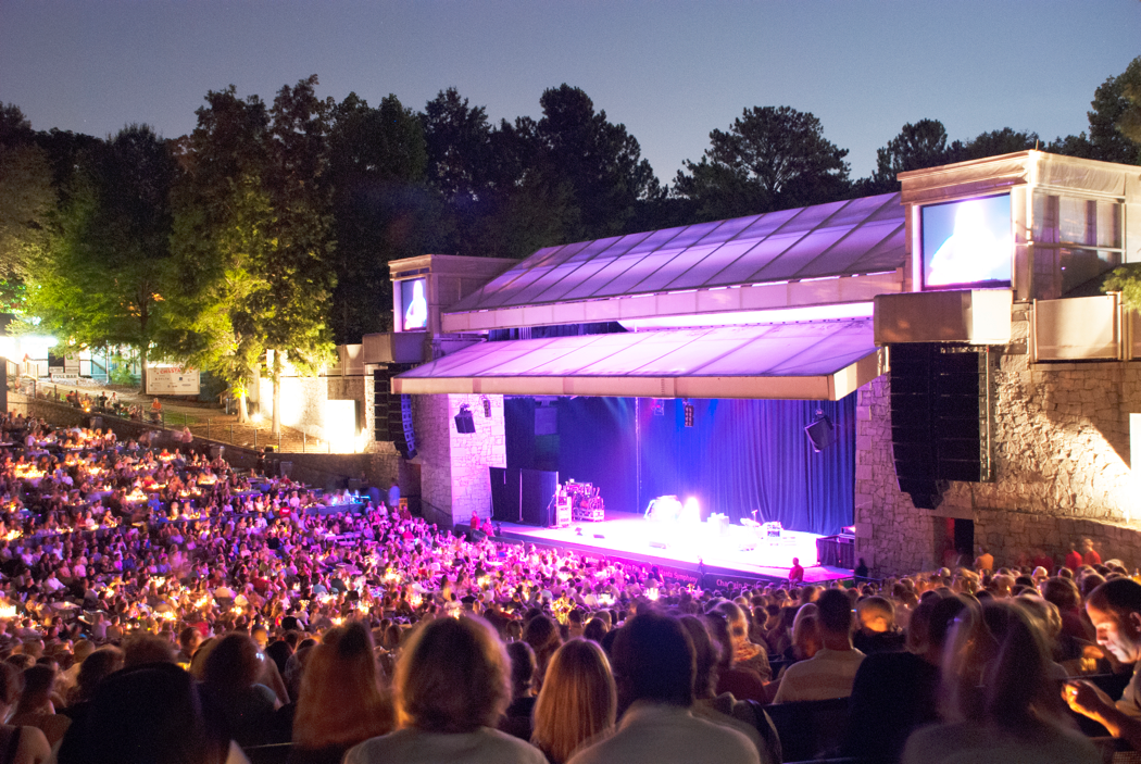 A photo of the stage, lit with a purple glow, is surrounded by concert-goers.