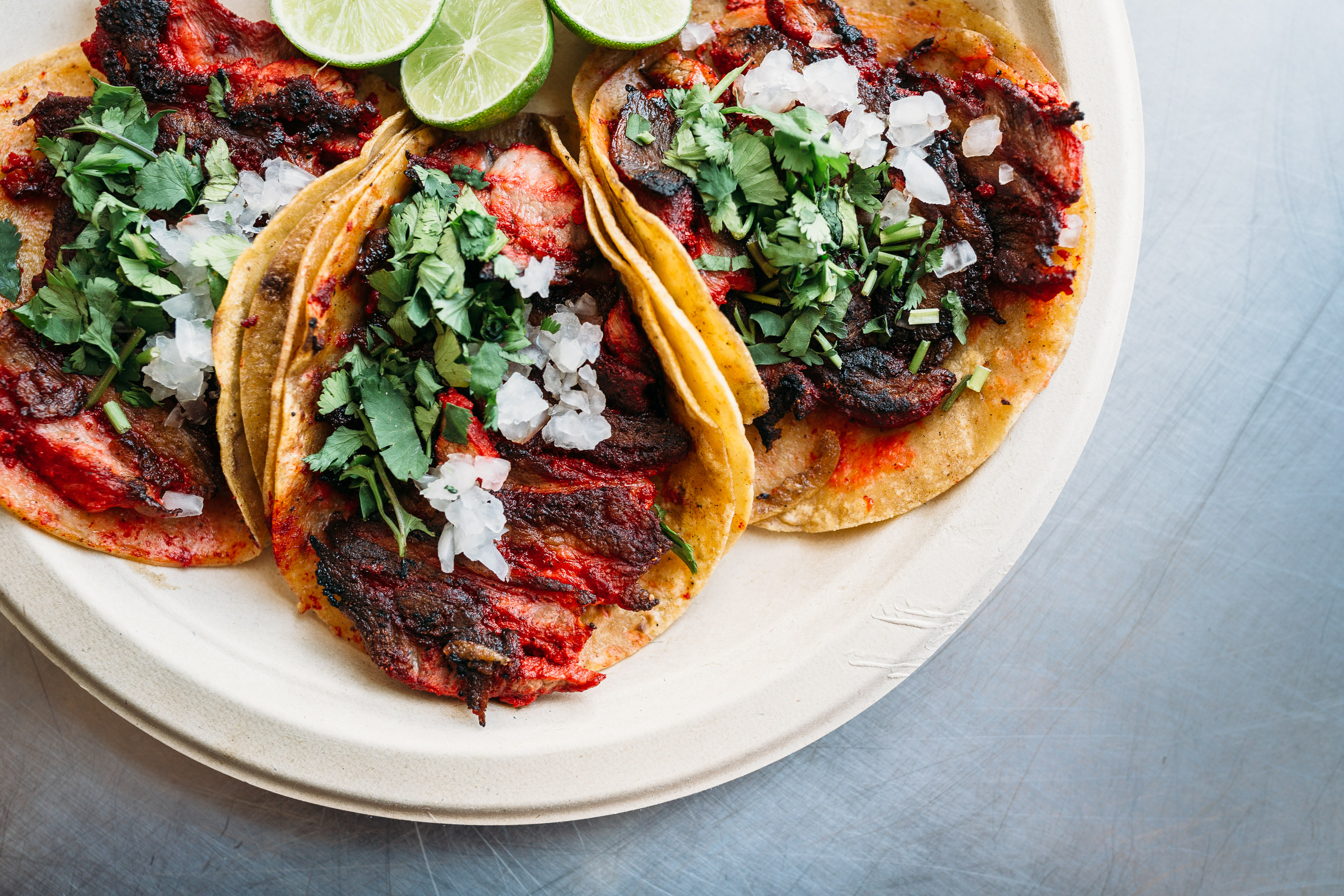 Tacos de trompo garnished with onion, lime, and cilantro