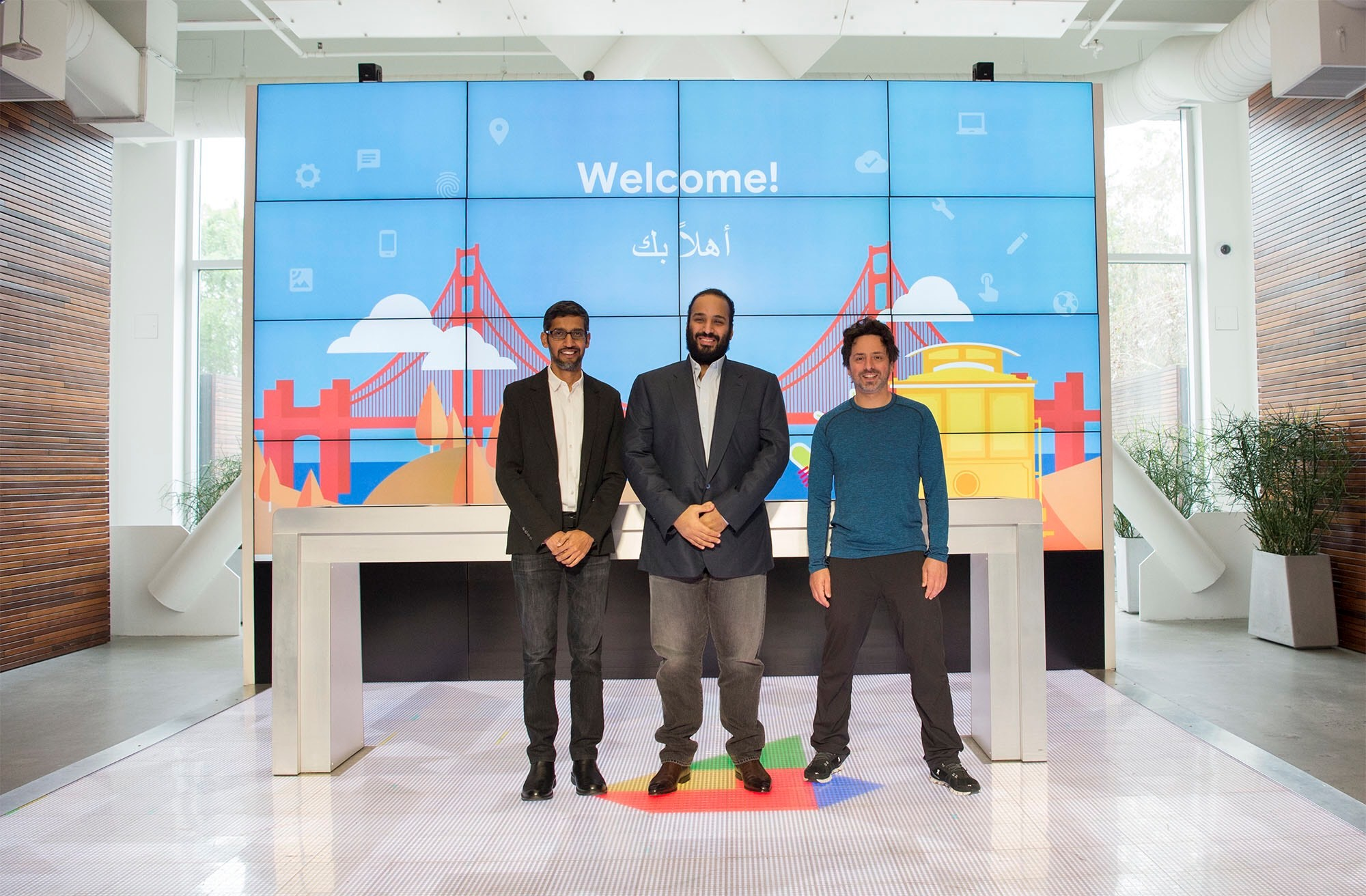 """left to right: Google CEO Sundar Pichai, Saudi Crown Prince Mohammed bin Salman and Google co-founder Sergey Brin pose in front of a """"Welcome"""" sign decorated with a drawing of the Golden Gate Bridge and a cable car."""