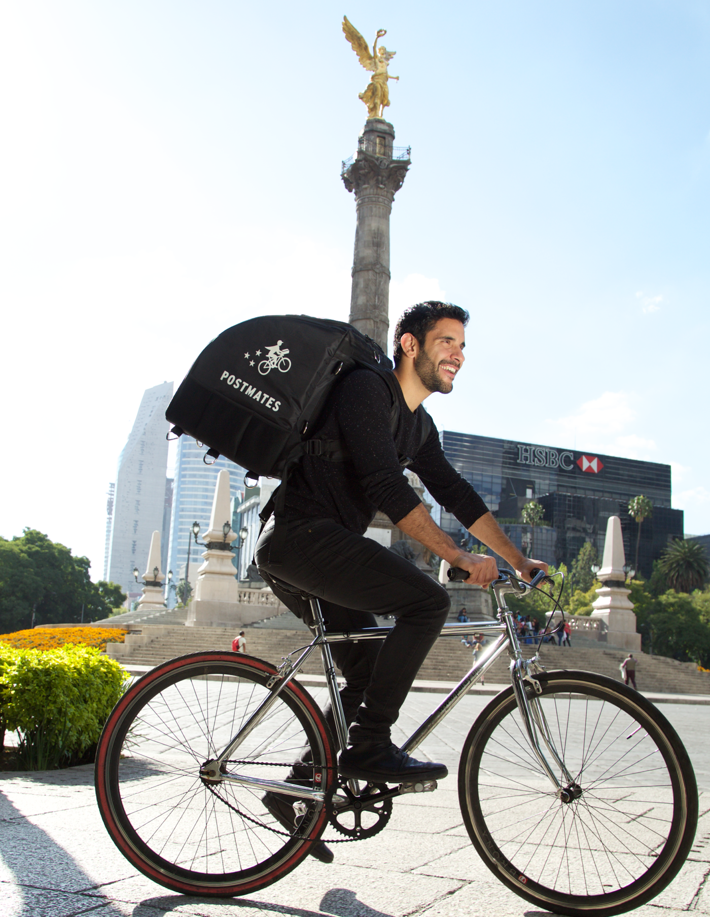 A Postmates delivery person riding a bike