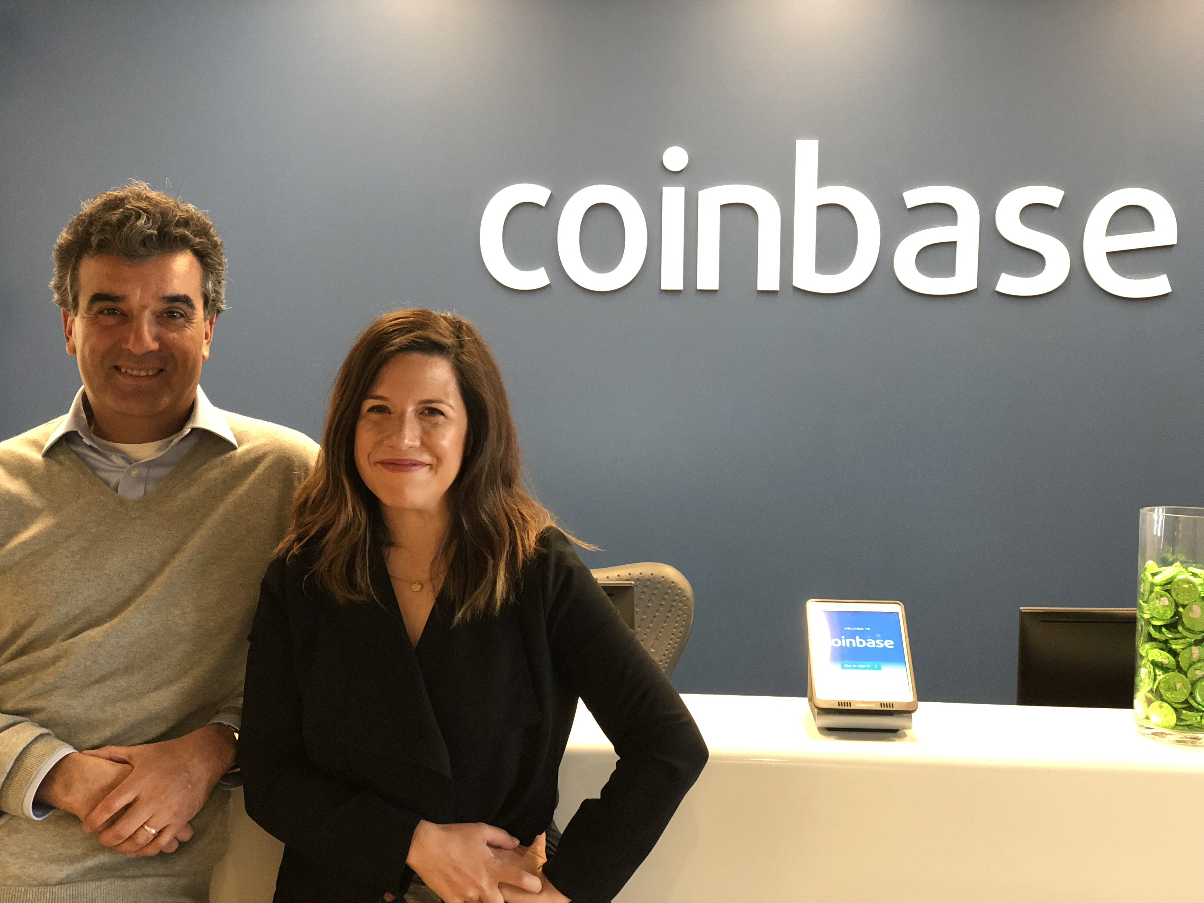 Coinbase COO Asiff Hirji (left) and VP of Communications Rachael Horwitz in front of the Coinbase reception desk