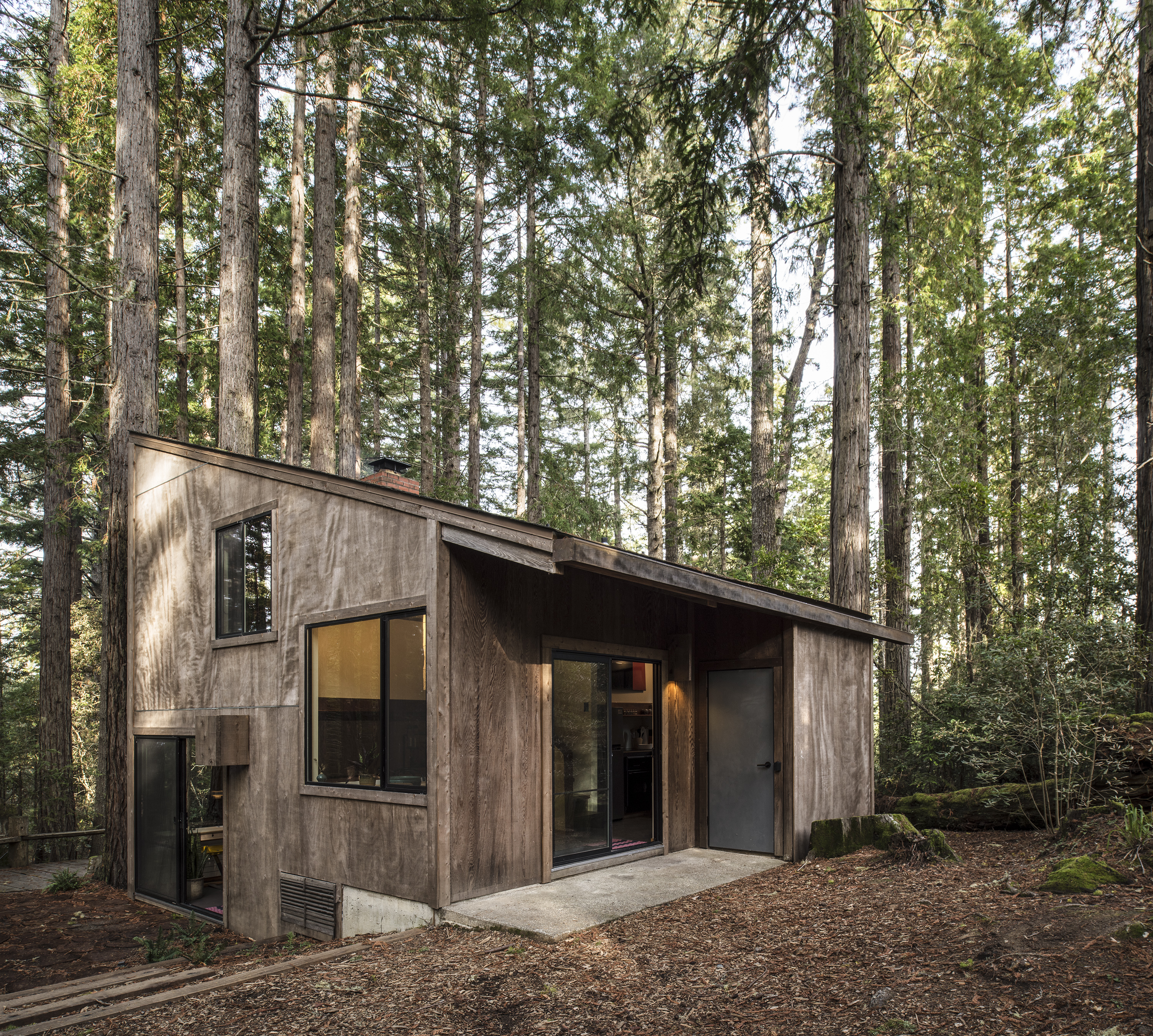 The exterior of a house. The house structure is comprised of wood. The house sits in a forest full of trees.