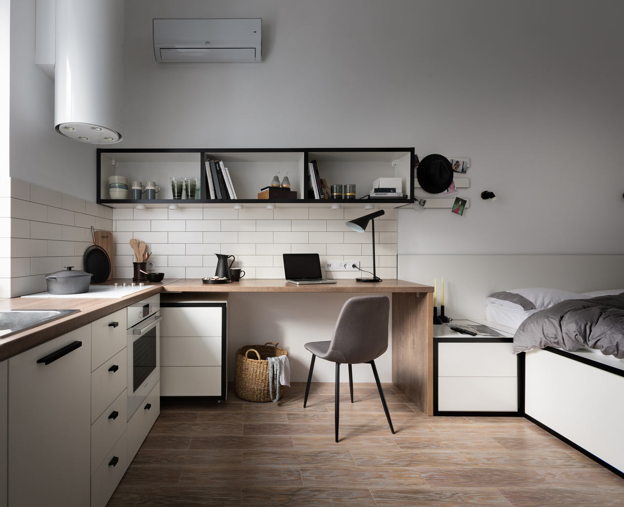 View of small one-room apartment with kitchen counter, desk, and built-in bed.
